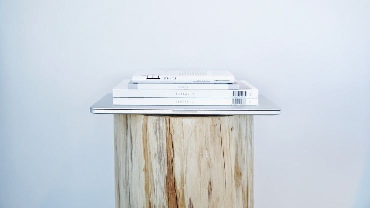 Three periodicals and a laptop sitting on a tree stump with white wall background.
