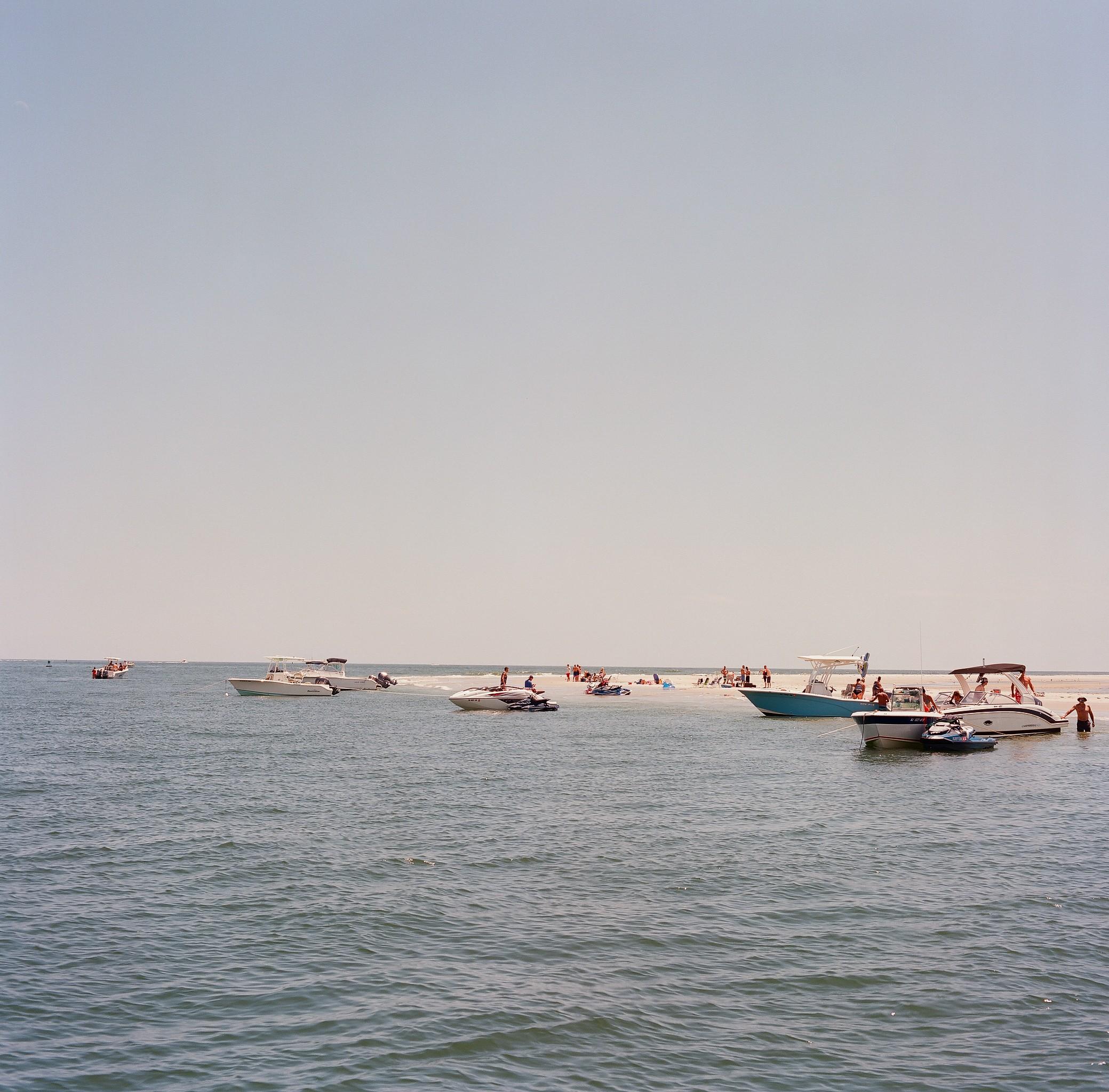 Boats gathered at a sandbar in the bay, shot on medium format film.