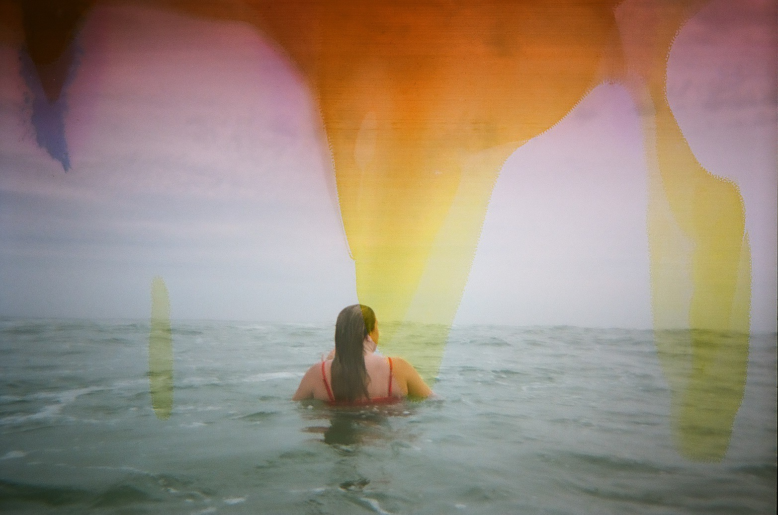 """35mm film photographed with a plastic """"waterproof"""" point and shoot from my childhood, colors caused by a salt water leak reacting with the film."""