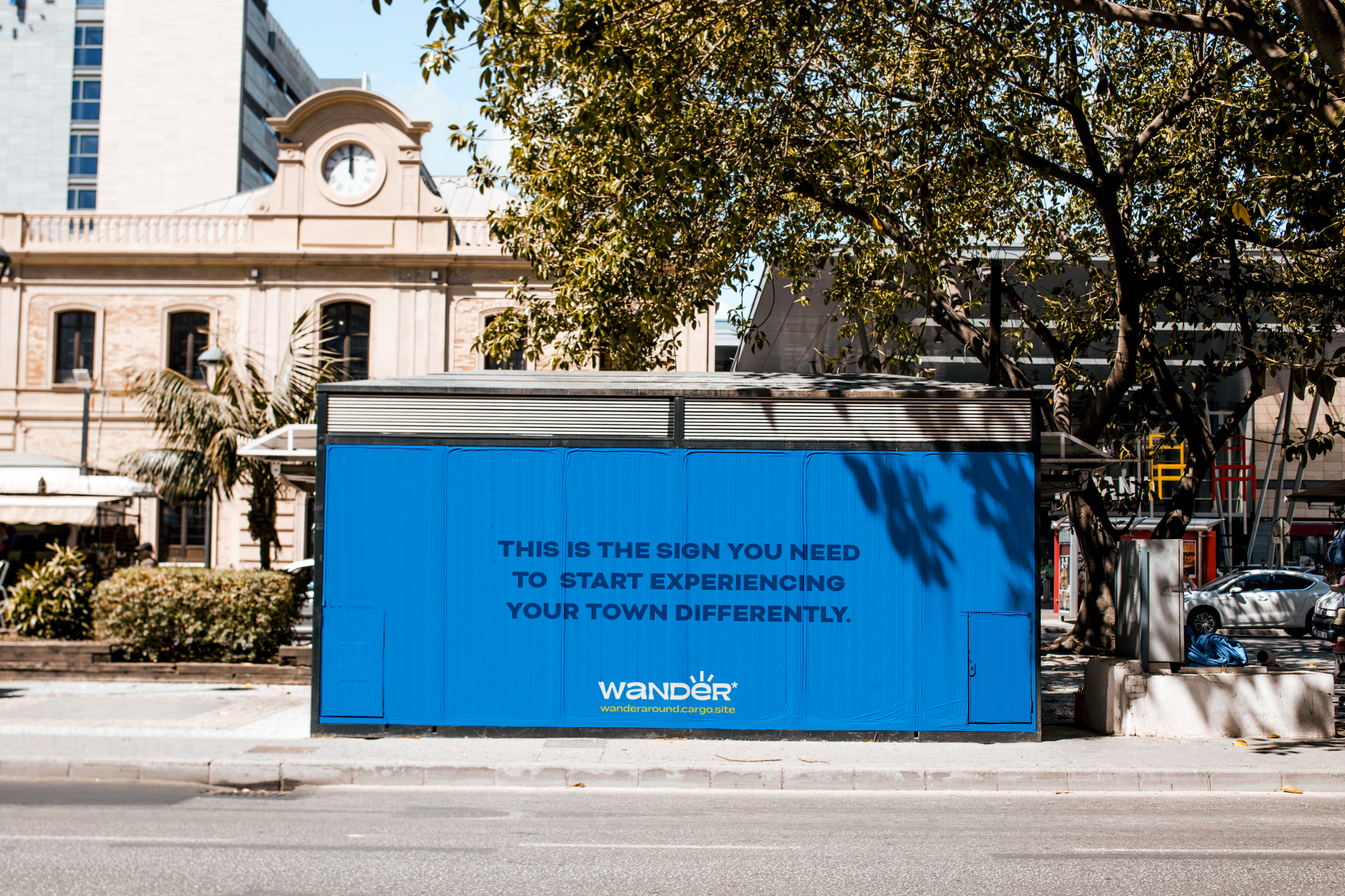 """Image depicts a city landscape with a kiosk in the middle, the kiosk has a sign that promotes the game Wander and says """"this is the sign you need to start experiencing your town."""" The sign is blue.  There's a tree and an old building with a cloc"""