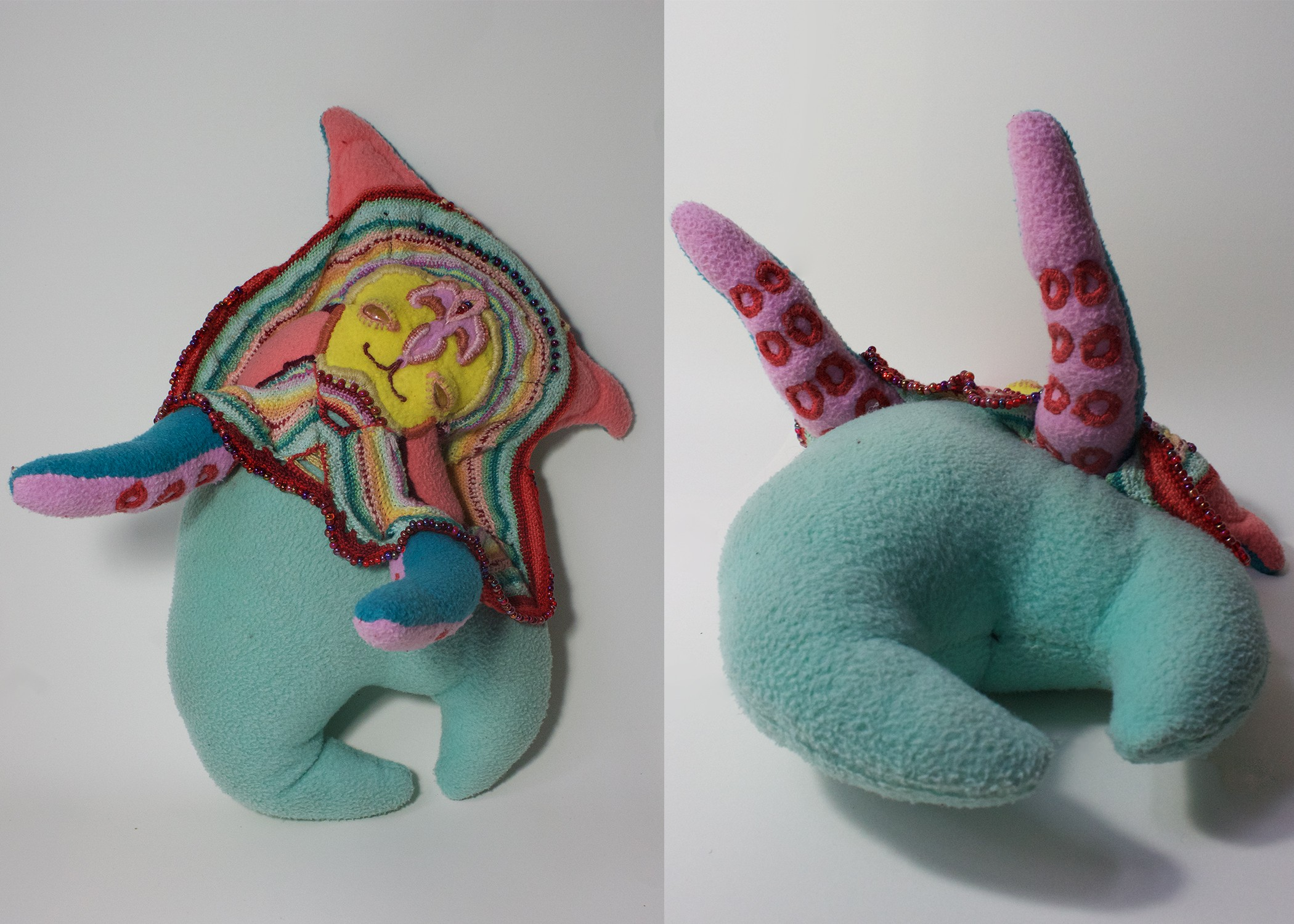 A soft sculpture creature, with a soft and kind smile, greets you with open arms. It has a bat-like face, round body, and two little octopus arms. The creature is mostly a soft teal, with a vibrant multicolored embroidered and beaded frill around its head