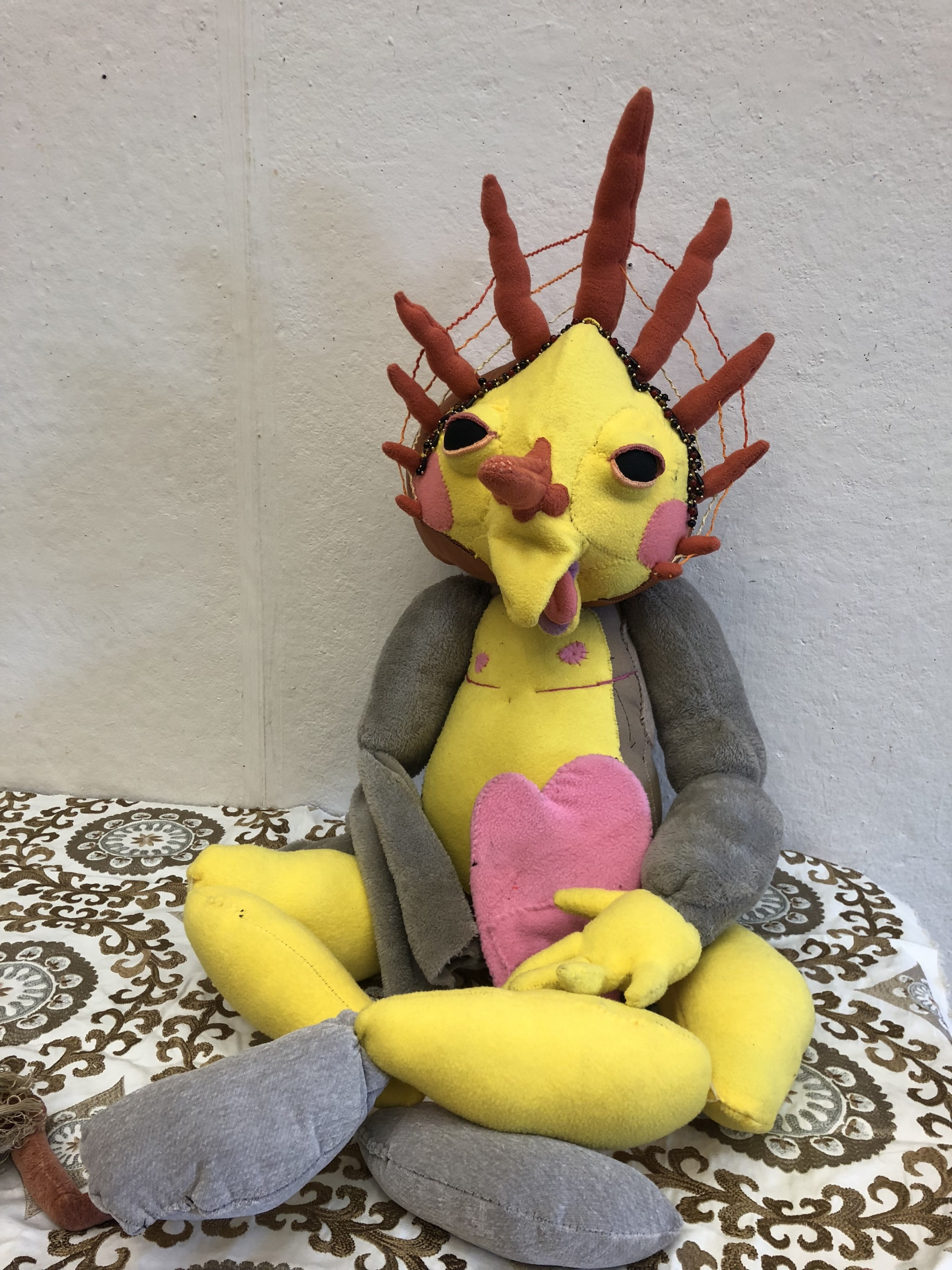A sun being puppet sits cross legged. His bright colors, embellishments, and prominent top surgery scars are meant to represent the immense self love I have found in accepting my identity as a trans person.