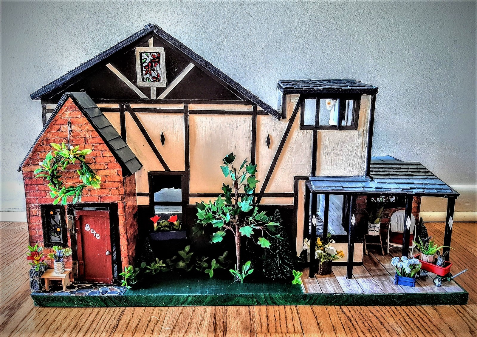 Three- dimensional wood replica of a tudor style house. Inside images are of the kitchen, living room, and upstairs.