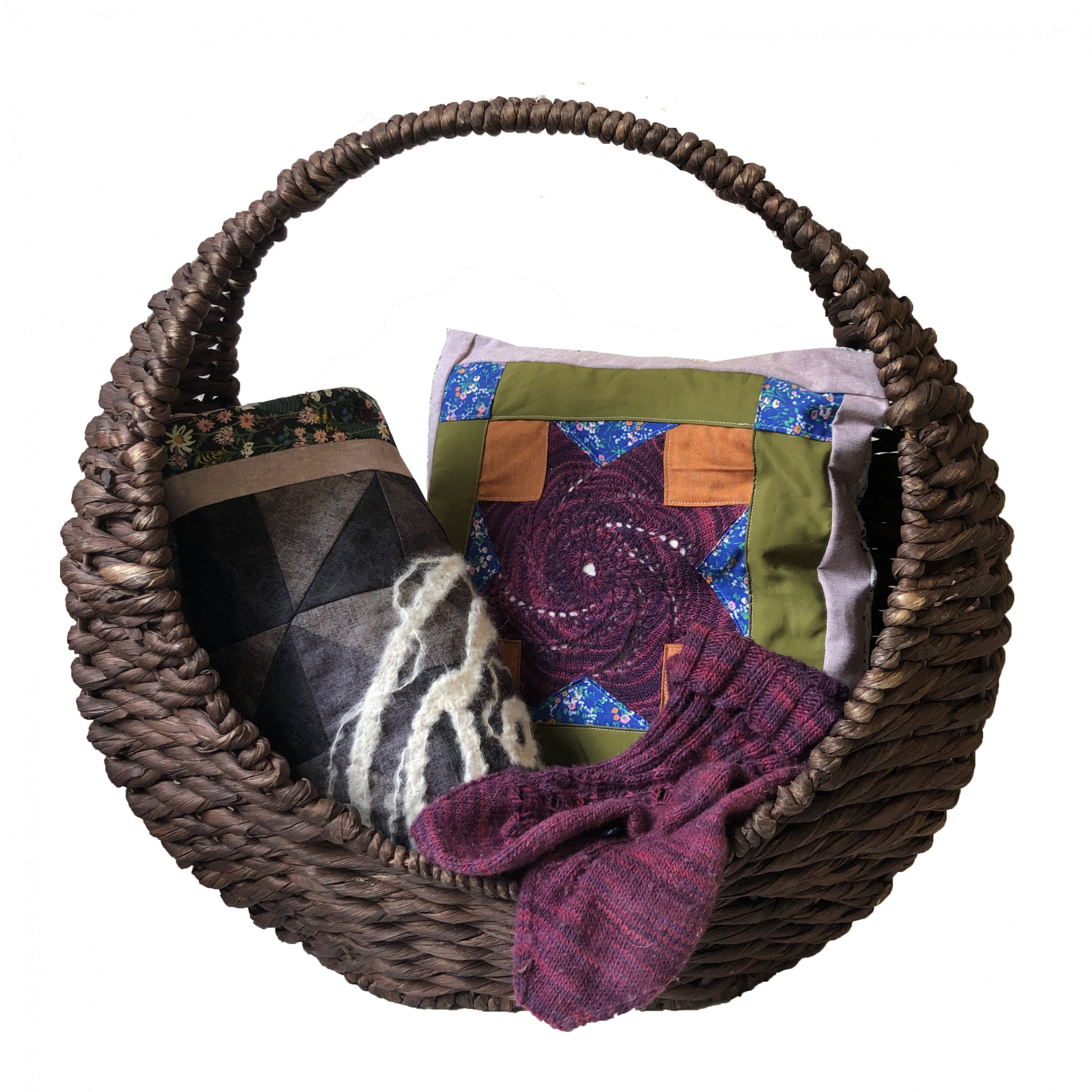 A crescent-shaped basket containing a pillow, a rolled up quilt, and a pair of socks.