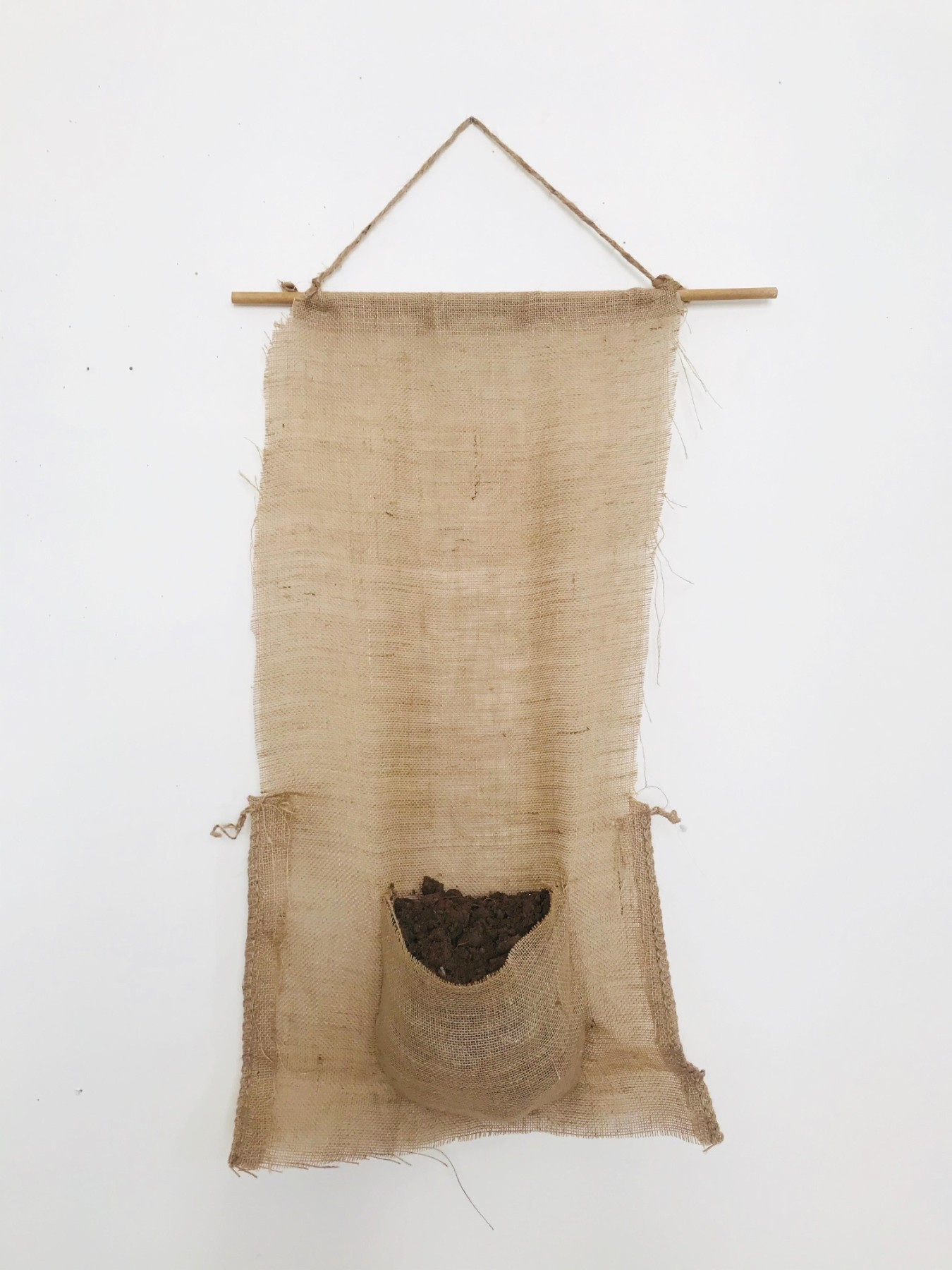 Burlap bag hanging on wall with pocket full of dirt dug up from ground