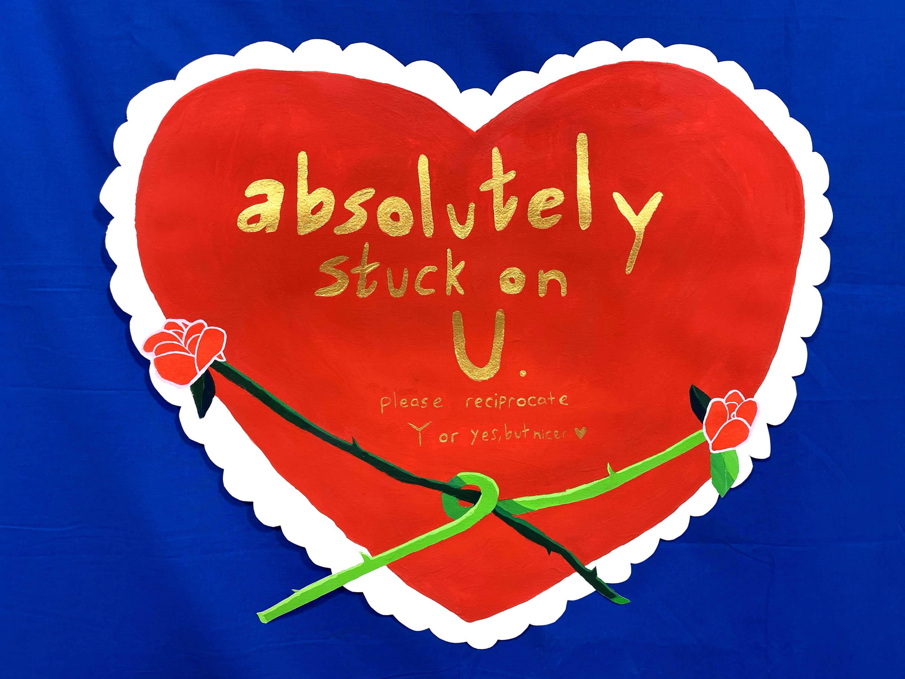 """This painting is in the shape of a large Valentine's heart. It's a vibrant red with a white scalloped trim. In the center are the words, """"absolutely stuck on U"""" in large metallic gold letters. In the same gold paint underneath the big words are smaller wo"""