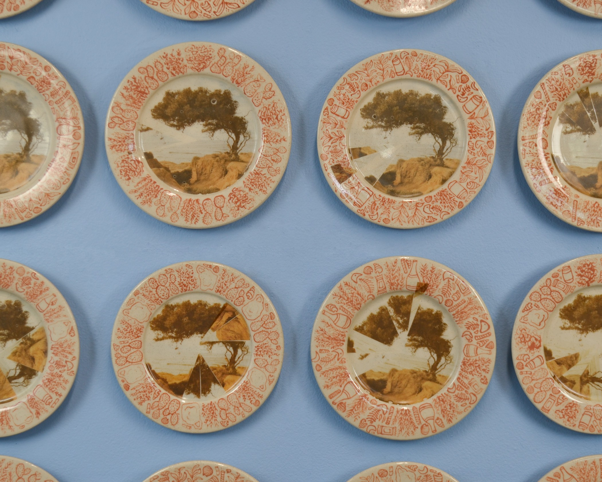 Cropped close up of 8 out of 16 ceramic plates. The plates are hanging on a sky-blue wall. Each plate is about 8 inches in diameter. The center of each plate is decorated with an image of a tree on a cliffside that overlooks the ocean. The image becomes i