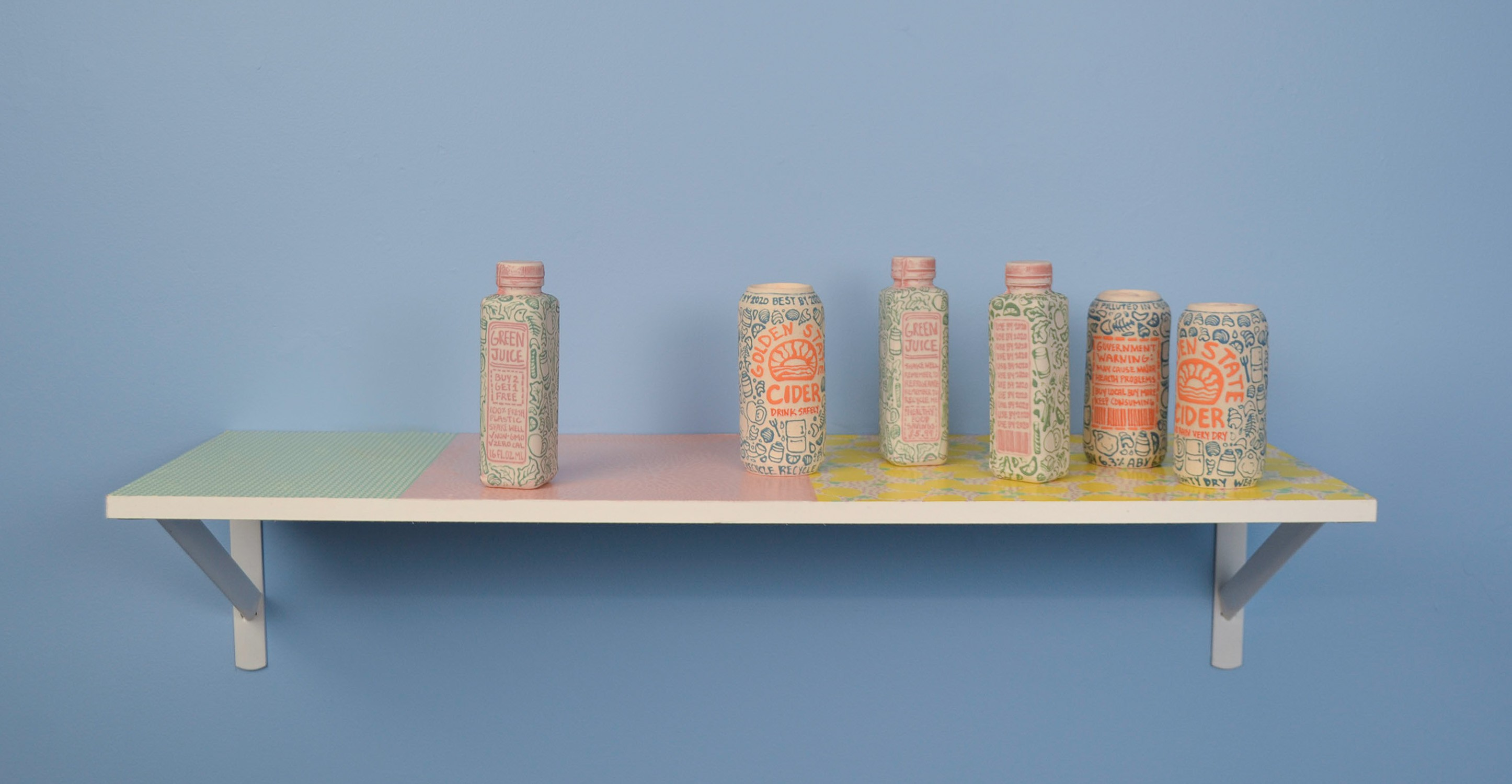 Full view of a shelf holding ceramic objects on a sky-blue wall. The objects, from left to right, are a bottle, a can, a bottle, a bottle, a can, and a can. The ceramic bottles are in the shape of rectangular bottles. The ceramic cans are in the shape of