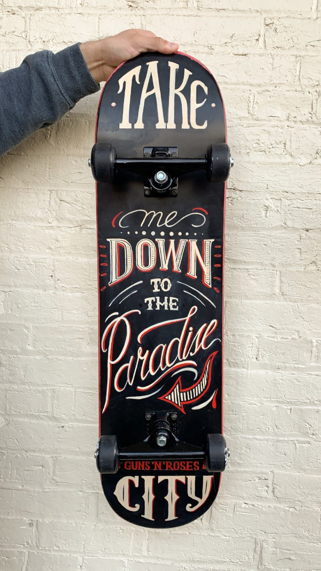 A phrase, hand lettered on the skateboard says 'Take me back to the Paradise city' and shows a variety of lettering styles.