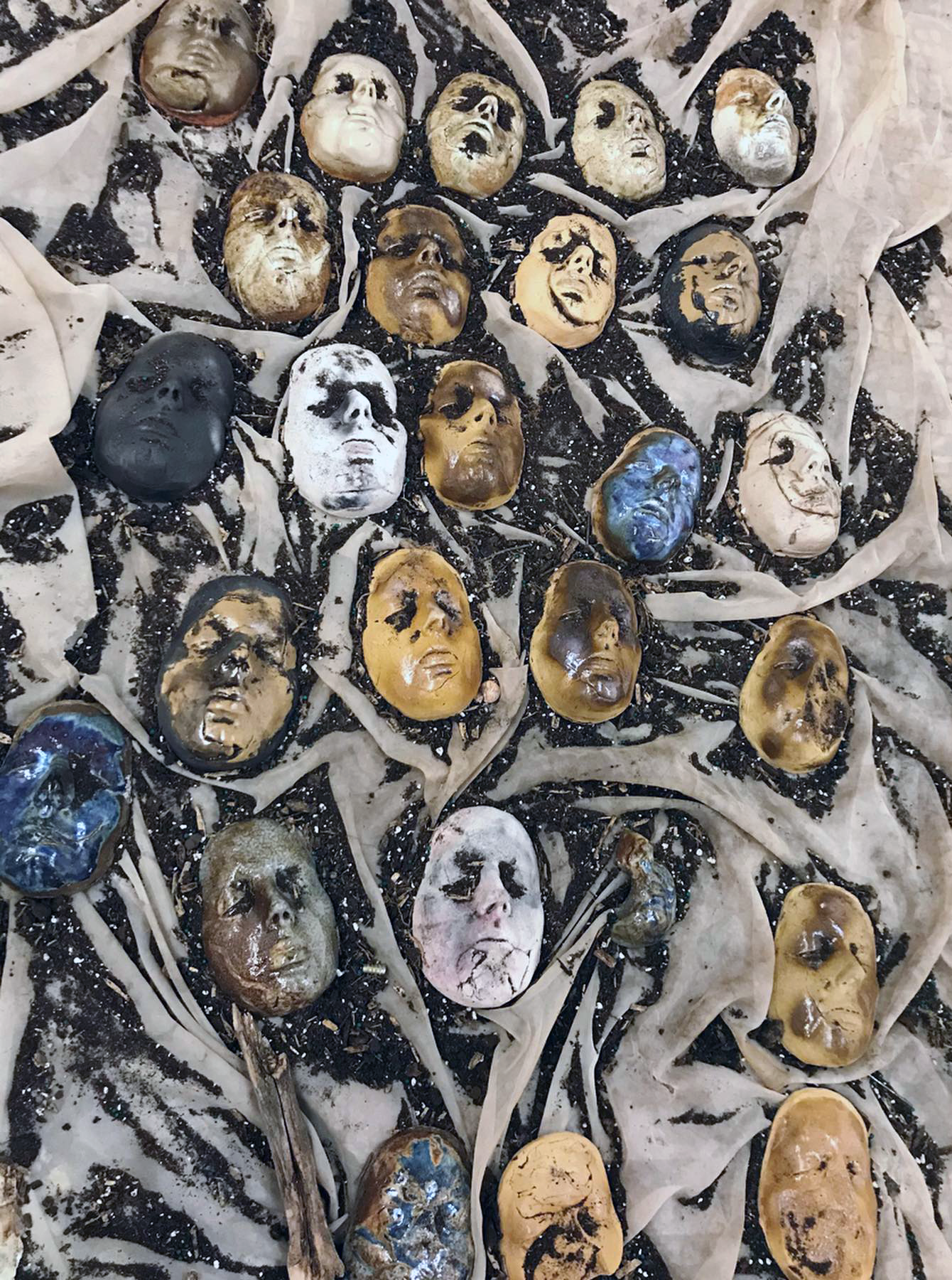 life cast of ceramic faces on soil and fabric with different personal items including jewelry, photographs and books