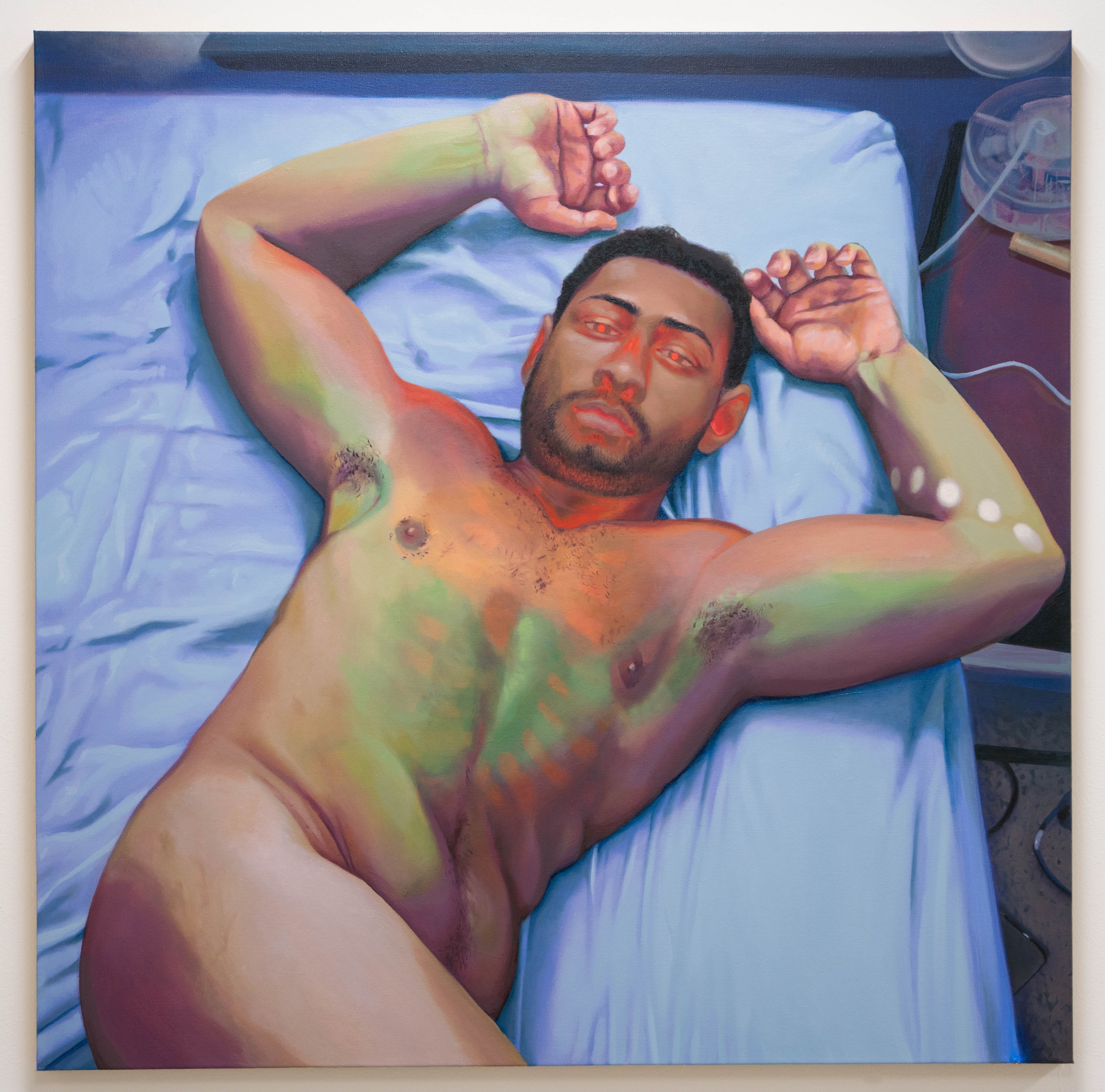 A 25 year old man relaxes, facing the viewer, in a submissive position. He is nude with the turn of his body and leg providing tasteful censorship. His eyes are glowing, inviting, looking directly at the viewer as his chest emits a green and orange glow.