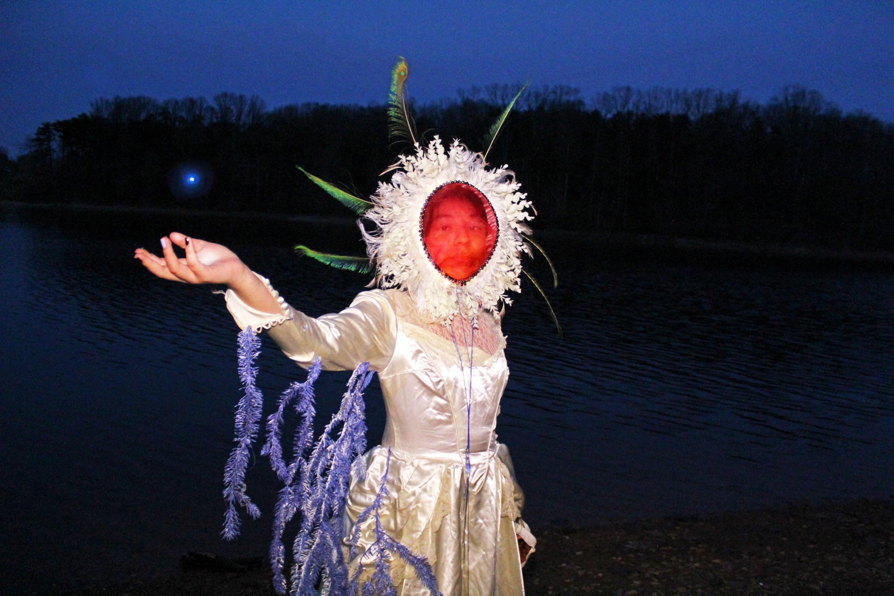 Person wearing a white wedding dress and holding an orb of light beside a river at night.