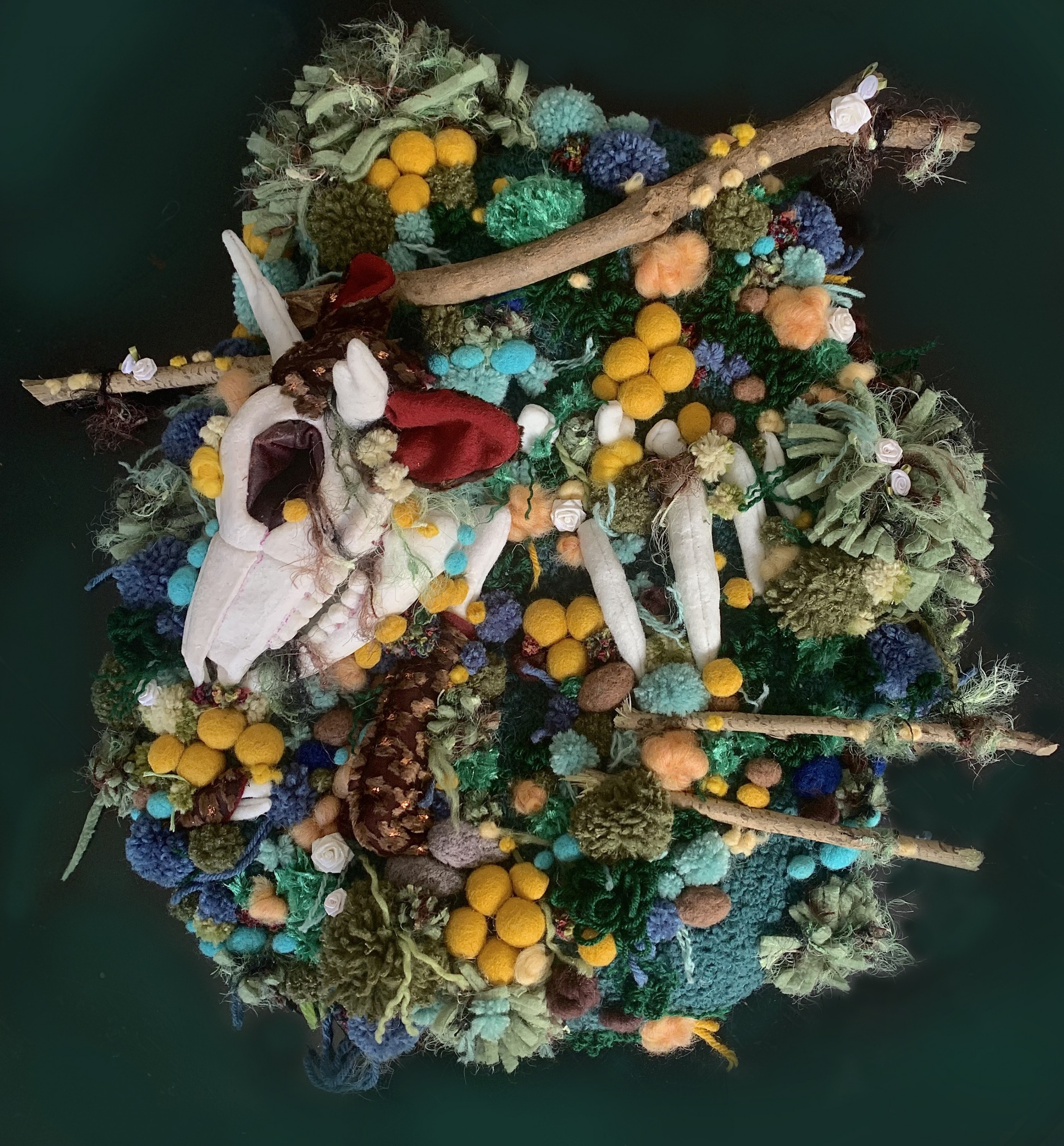 A fabric skull with horns and ears is resting in a bed of pompoms. The pompoms are various colors of blue, green, brown, and yellow to resemble fungi. There are several sticks poking out from the pompoms, and the sticks have small white flowers and yarn t
