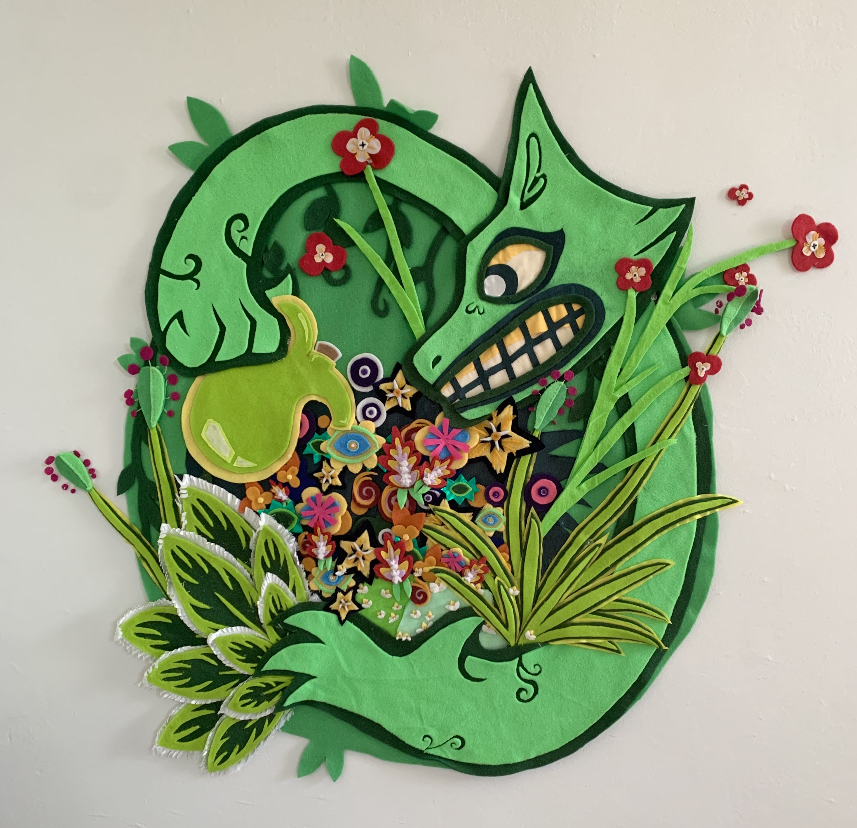 The piece is green and circular. A large bright green dog with yellow eyes and teeth and swirly vine markings on its wrists has its arms stretched around the edge of the whole piece. He is holding a lime green watering pot in his left hand, pouring water