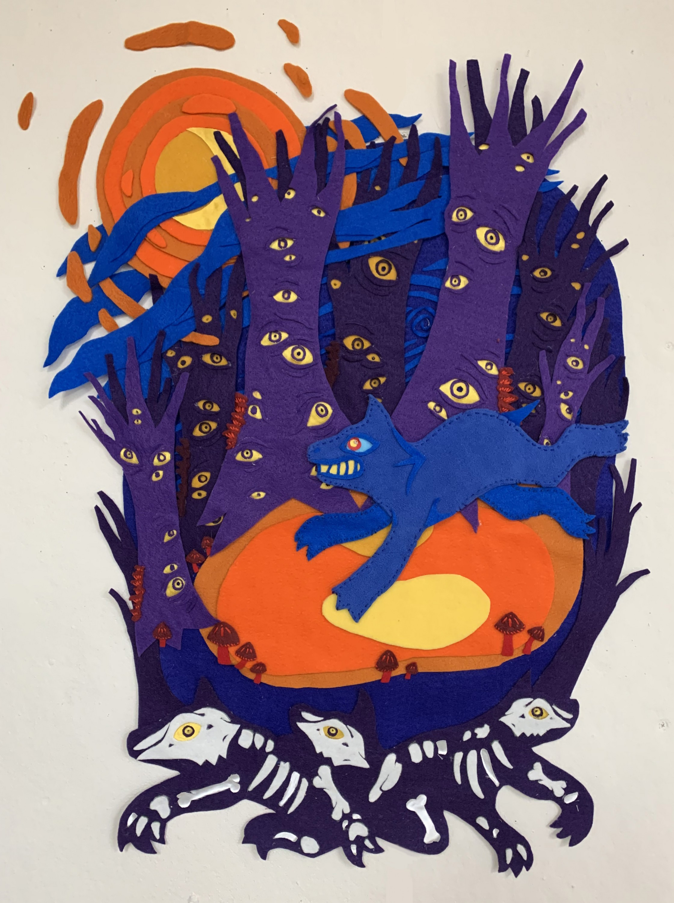 There is a bright blue dog running through a forest of dark purple trees resting on a bright orange ground. The trees are covered in golden yellow eyes that follow you when viewing the piece. Below the orange ground there are several skeleton dogs with ye