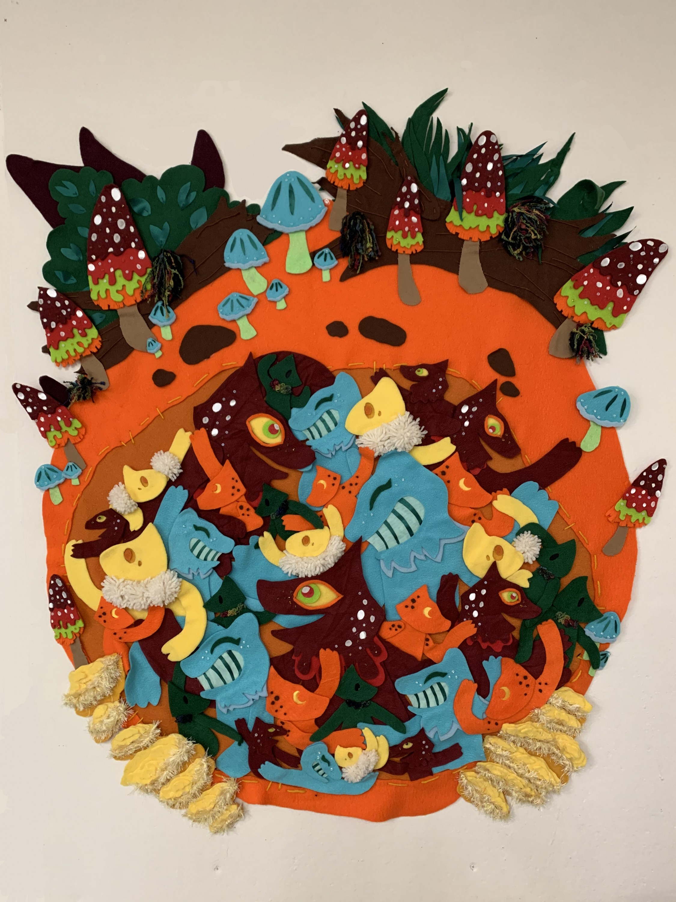 A large circular piece made with bright orange fabric, decorated with grass, logs, and mushrooms at the top. At the bottom there are clusters of yellow oyster mushrooms. The circle is cut out in the middle and has a darker orange background, and in the cu