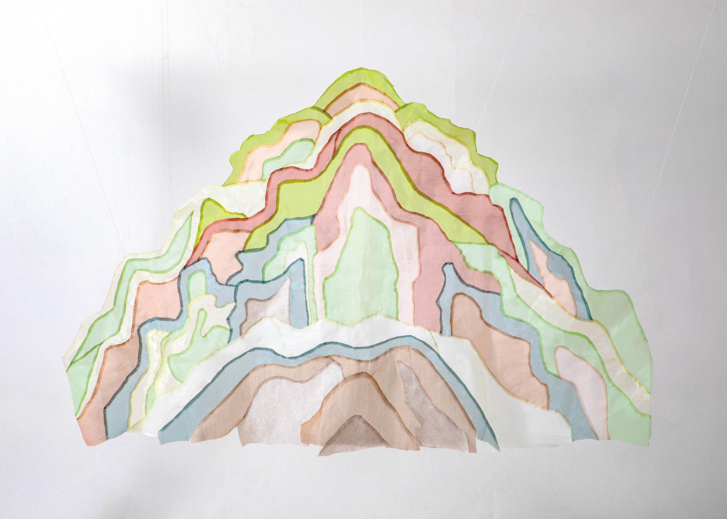 A mountain peak of pink, yellow, green, and blue pieces of fabric.