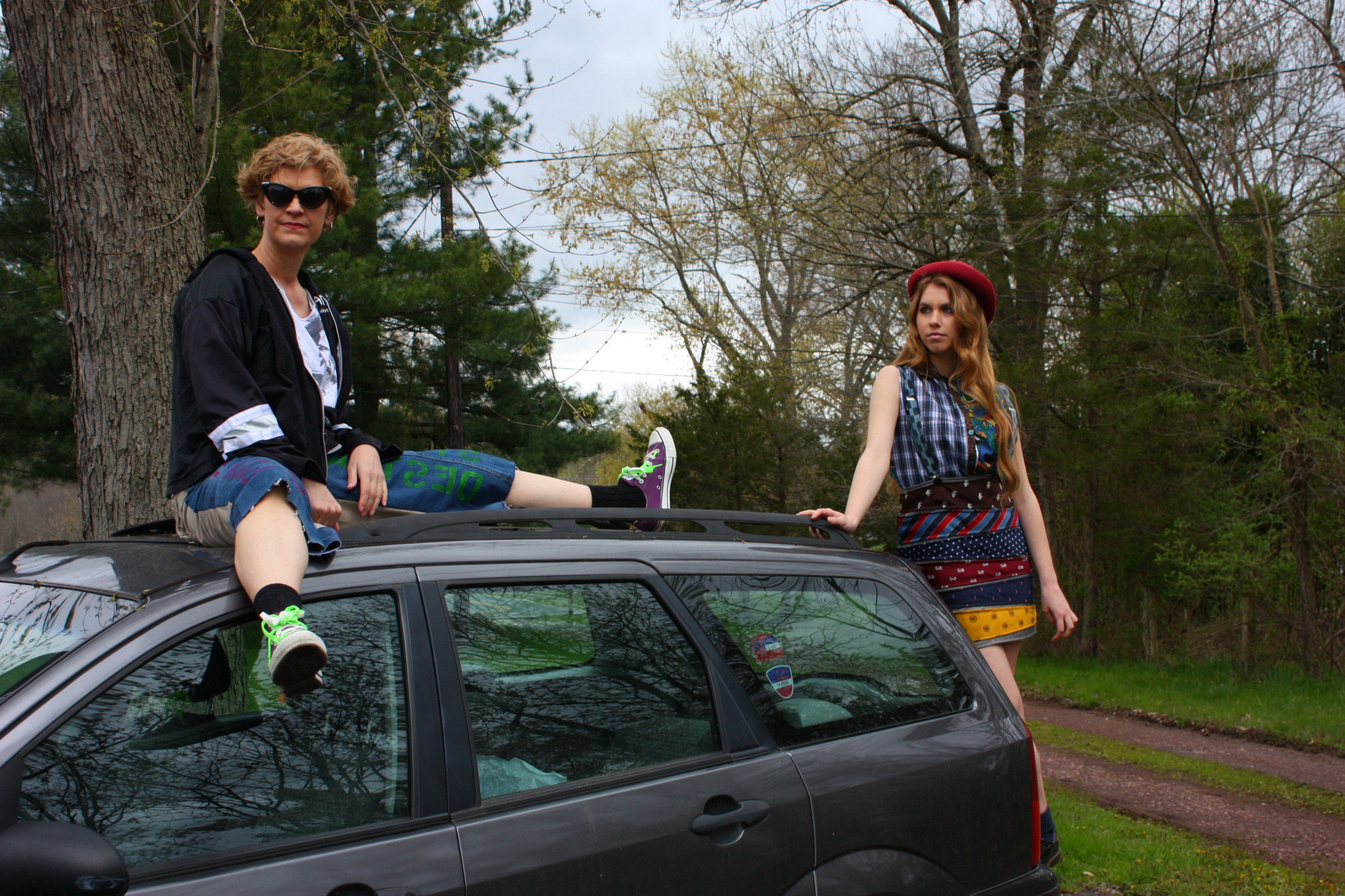 Skate Punk model and Ska Punk model are positioned together. The Skate Punk model is sitting on top of a worn car and the Ska Punk model is position to the back side of the car.
