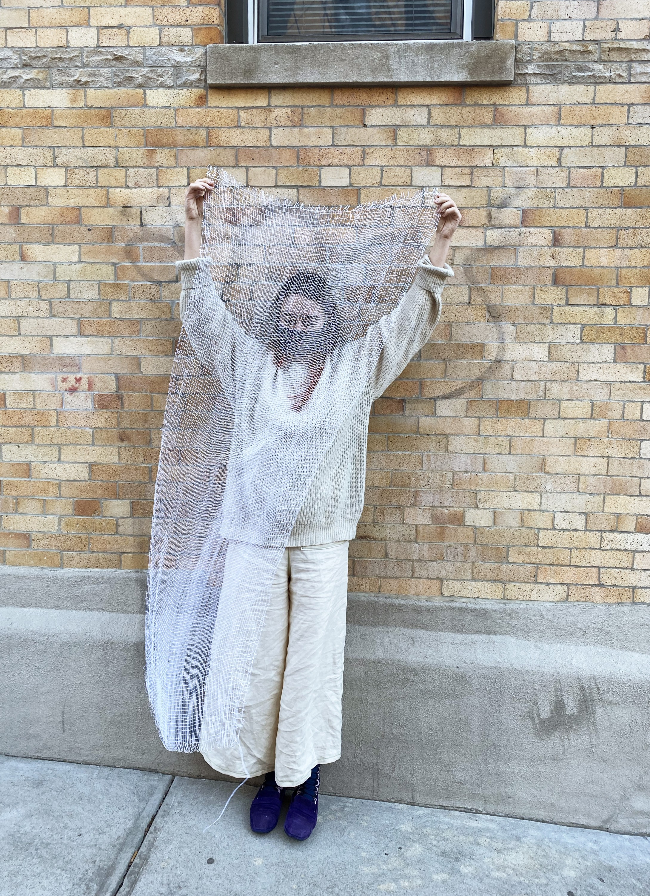 The artist holds loosely knit four selvage weaving in front of her, it is roughly her height and somewhat obscures her body. She stands in front of a brick building beneath an exterior window to demonstrate the size of the weaving in comparison to her own