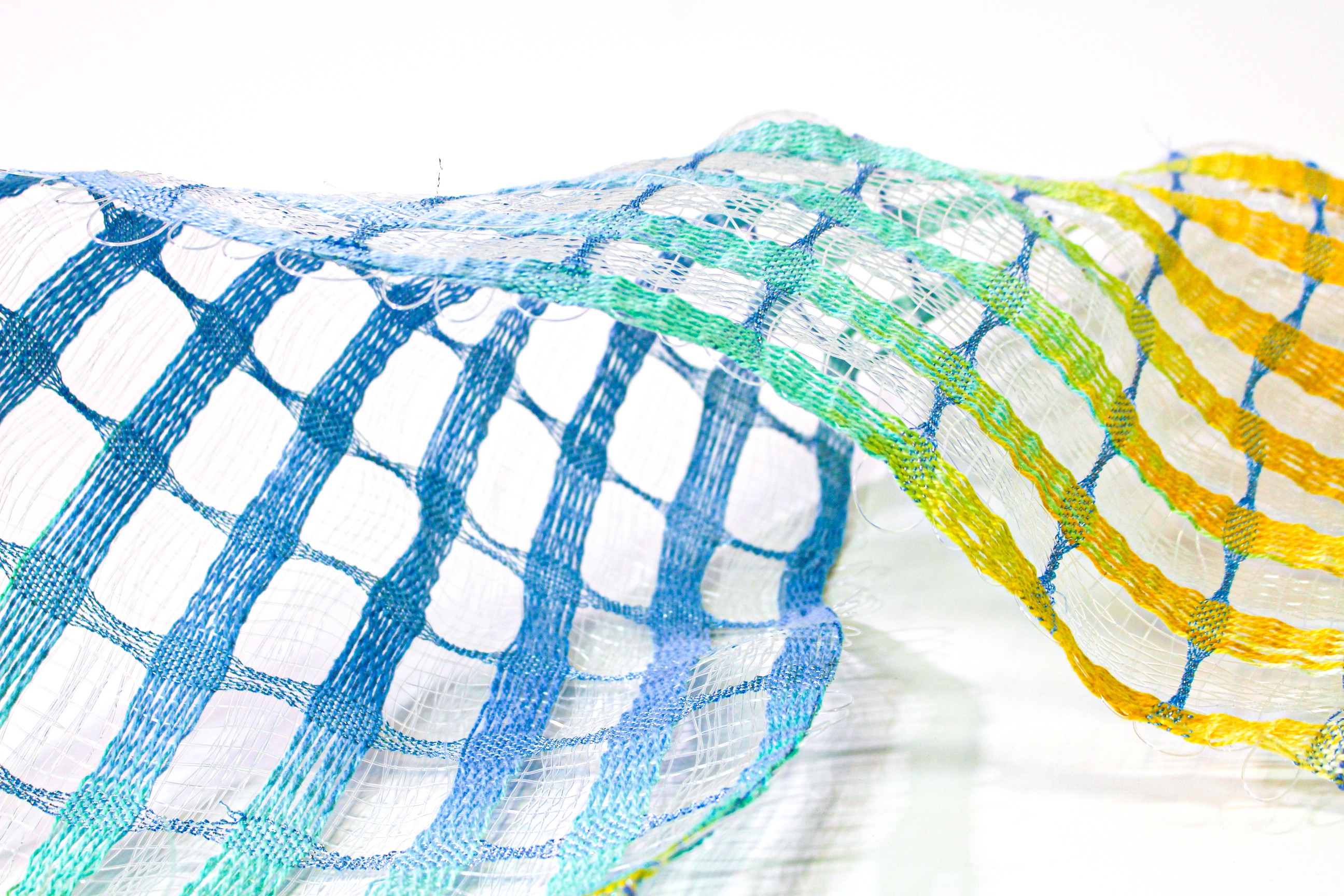 Woven fabric lies horizontally across the plane. The fabric is broken into bands that have a color gradation of blue, green, and golden yellow. In between these sections is transparent fishing line that softly reflects light.