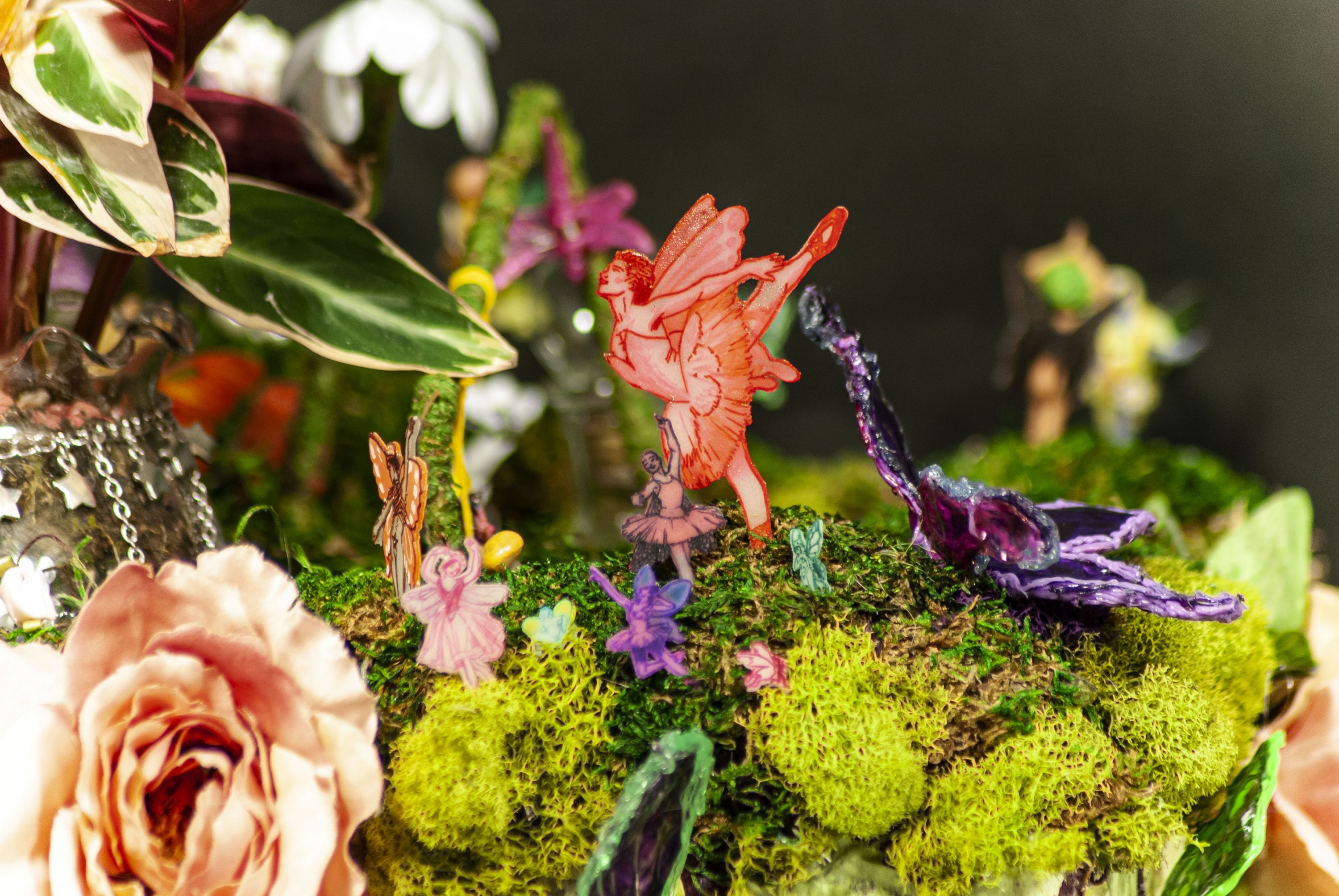 Image of a purple block with green bricks and green moss on top that displays miniature sculptures of pixies. There are three swings, a white flower, and a large pink monkey present in the surrounding foliage.
