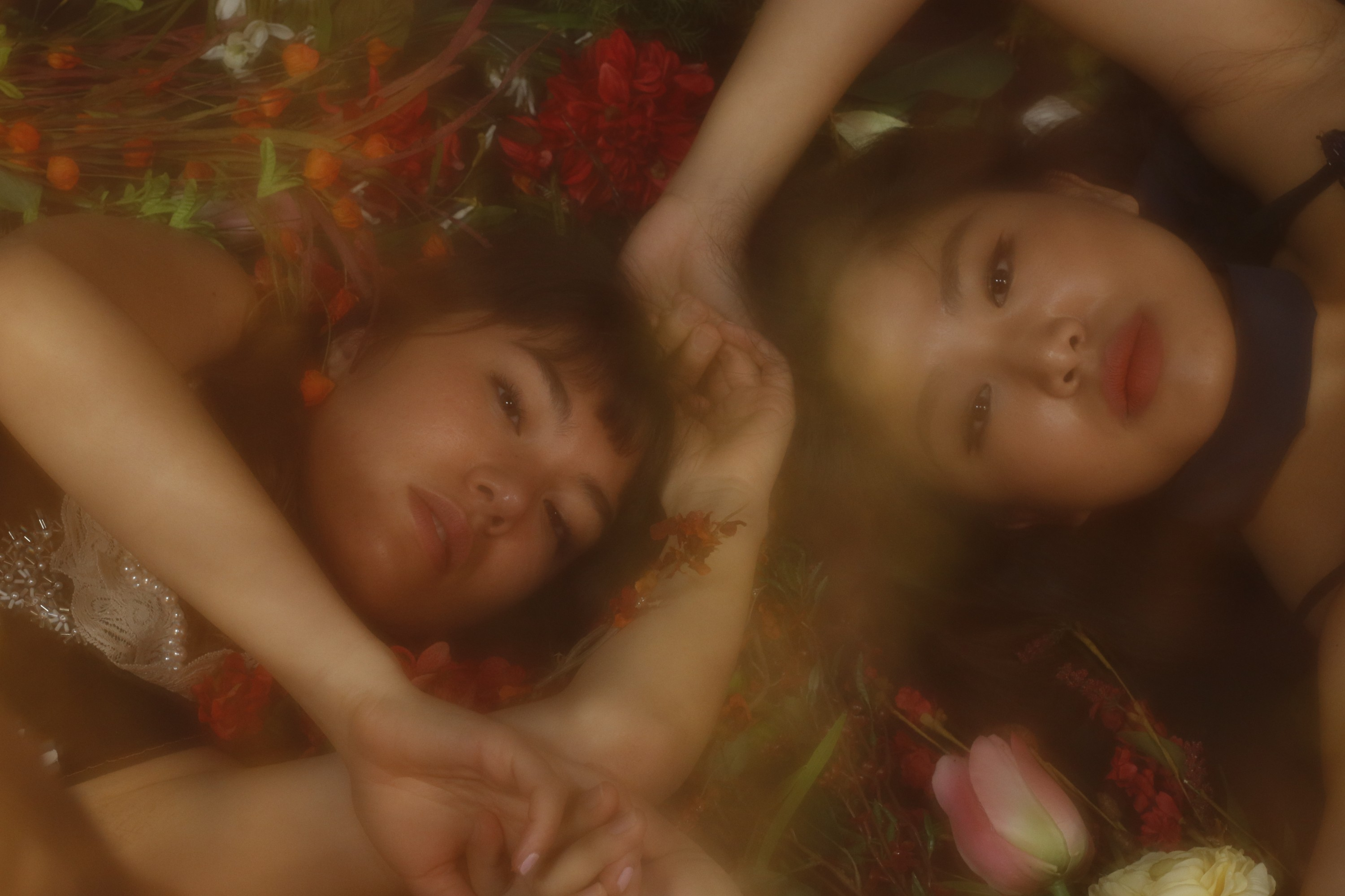 Two girls lie under a film seemingly under a layer of water. They grasp hands over their heads and look directly at the camera.
