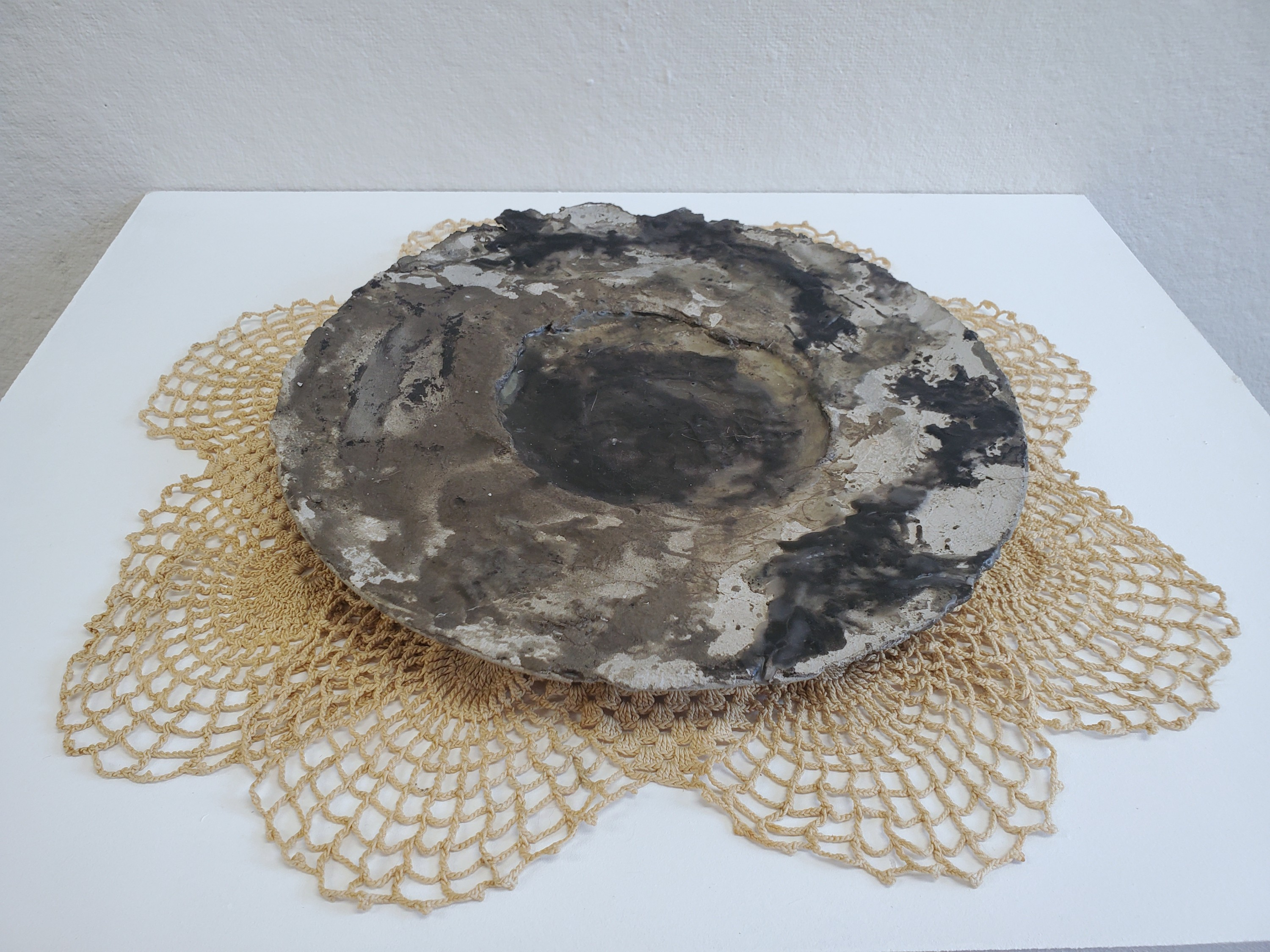 A plate on a placemat. The Plate is cement and wax. The wax is sticking broken pieces of the plate back together. The wax looks dirty and black is several places. The placemat is circular and is made of lace doilies dyed a light reddish brown with rust.