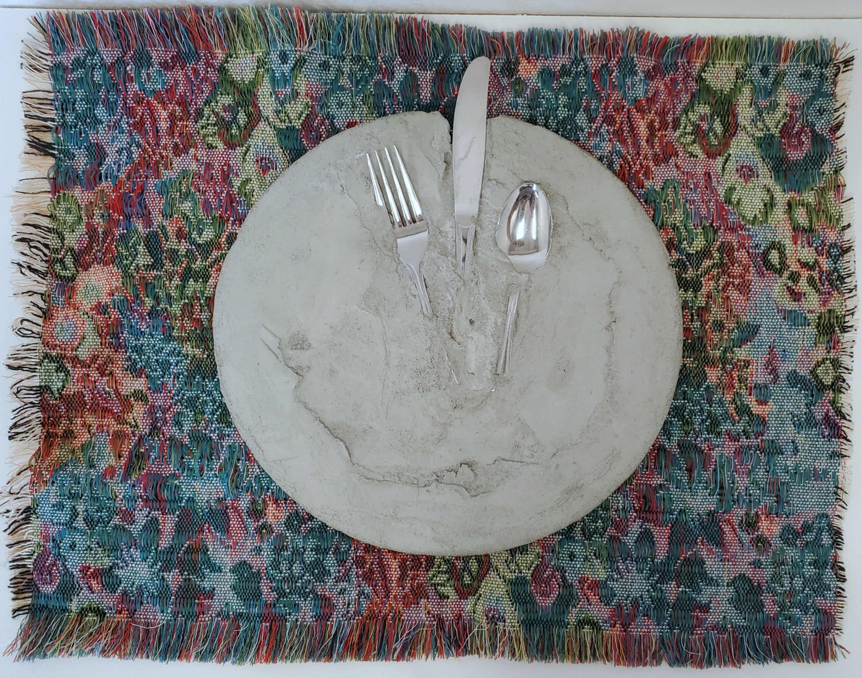 A plate on a placemat. The plate is cement with a fork, knife, and spoon Imbedded in it. The placemat is a rectangle, multicolored jewel toned floral. It is the wrong side of the fabric. It has fringed edges all around.