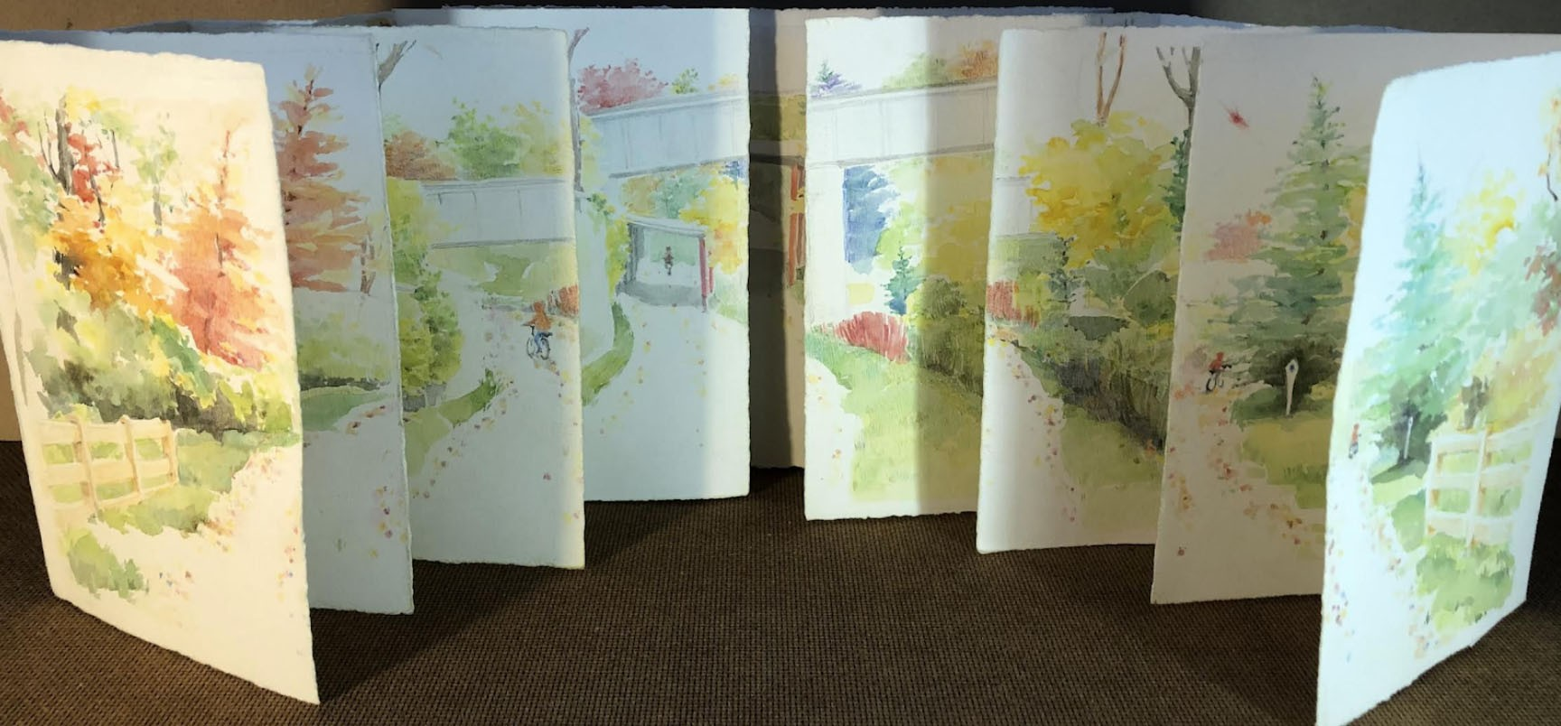 This is a book arts project that depicts a a bike trail in the fall. Each page portrays a a cyclist going further and further along the trails.