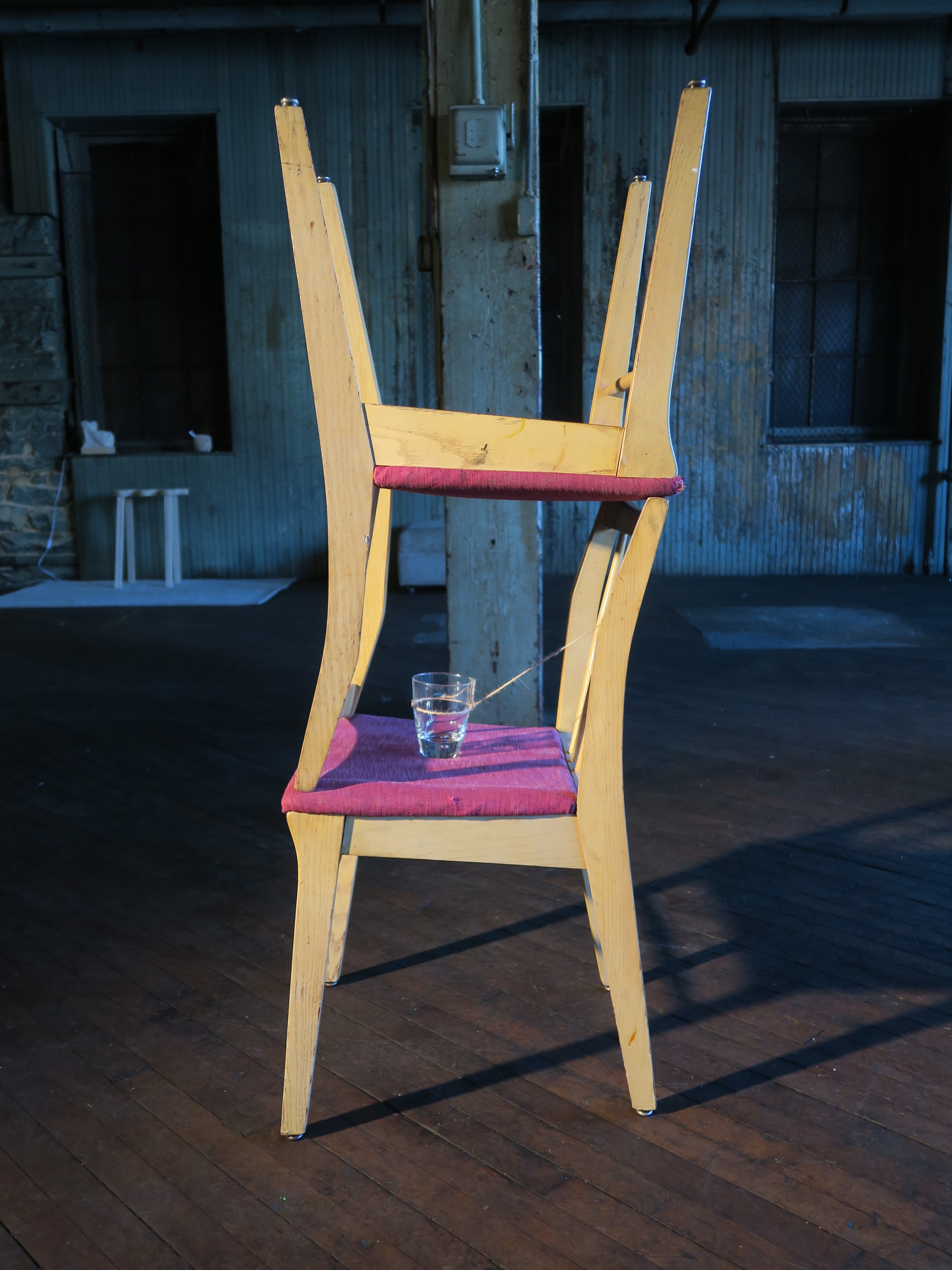Two chairs - one stacked inverted on the other. A plate with canned sardines, a fork and a knife is placed inside the space underneath the seat of the inverted chair. The plate is tied with a twine which connects to a glass of water placed on the seat of