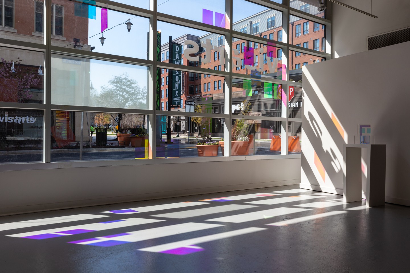 Colored film placed on the windows of the Gibbs Gallery at VisArts Center in Rockville, MD creates dramatically colored shapes on the floor as the light streams through in late afternoon.