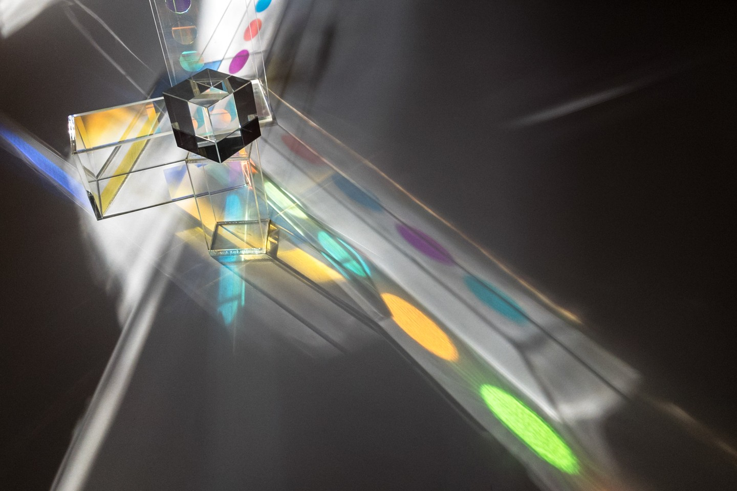 Acrylic sculpture with colored film and crystal cube, activated by light.