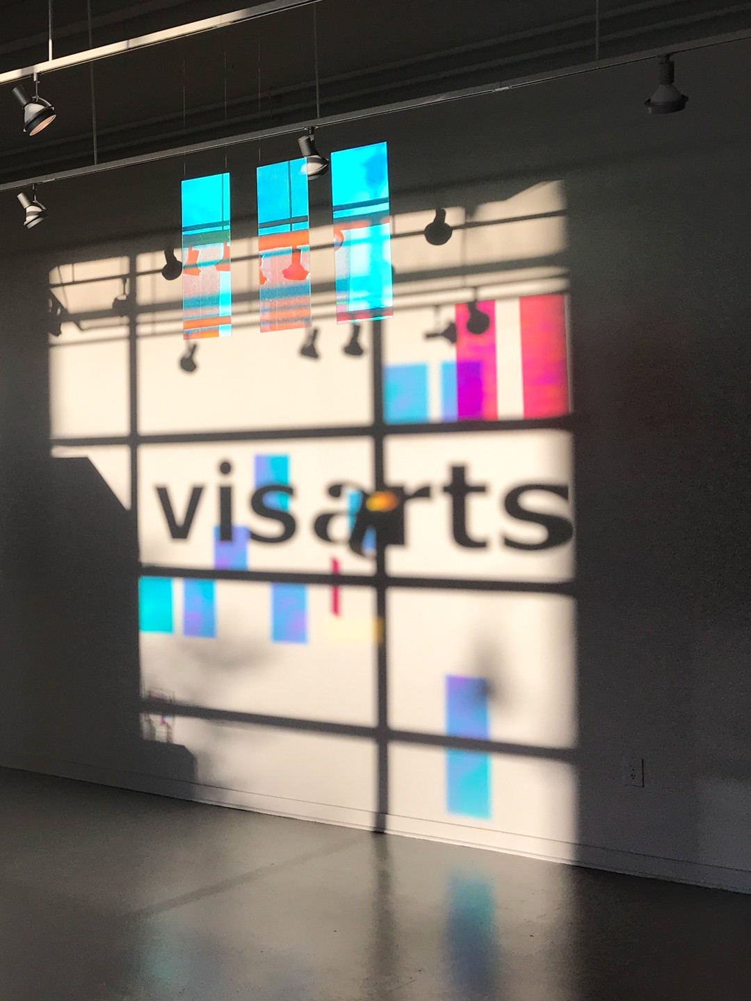 Three acrylic panels with dichroic film are suspended from the ceiling in evening light, projecting dramatically colored shadows on to the back wall of the Gibbs Gallery.