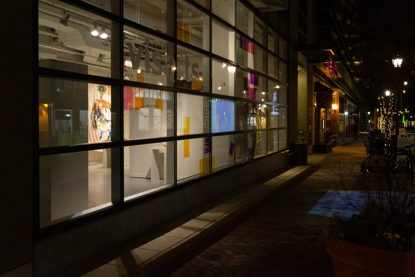 Colored film placed on the windows of the Gibbs Gallery at VisArts Center in Rockville, MD is seen from the exterior at night. A video projected through translucent film on the interior of the window can be seen from outside and on the sidewalk below.