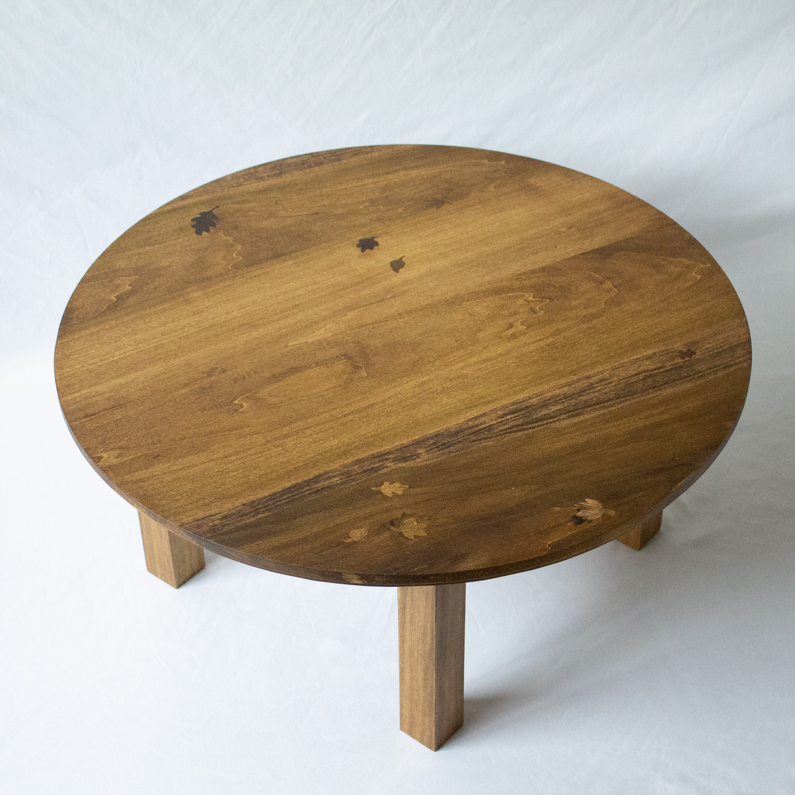 A dark walnut stained low round coffee table made of poplar wood. Reminiscent of traditional Korean low tables, it is perfect for sitting at at just 14 inches tall, while also sporting carvings on the face of each apron. The table-top has 12 leaf poplar w