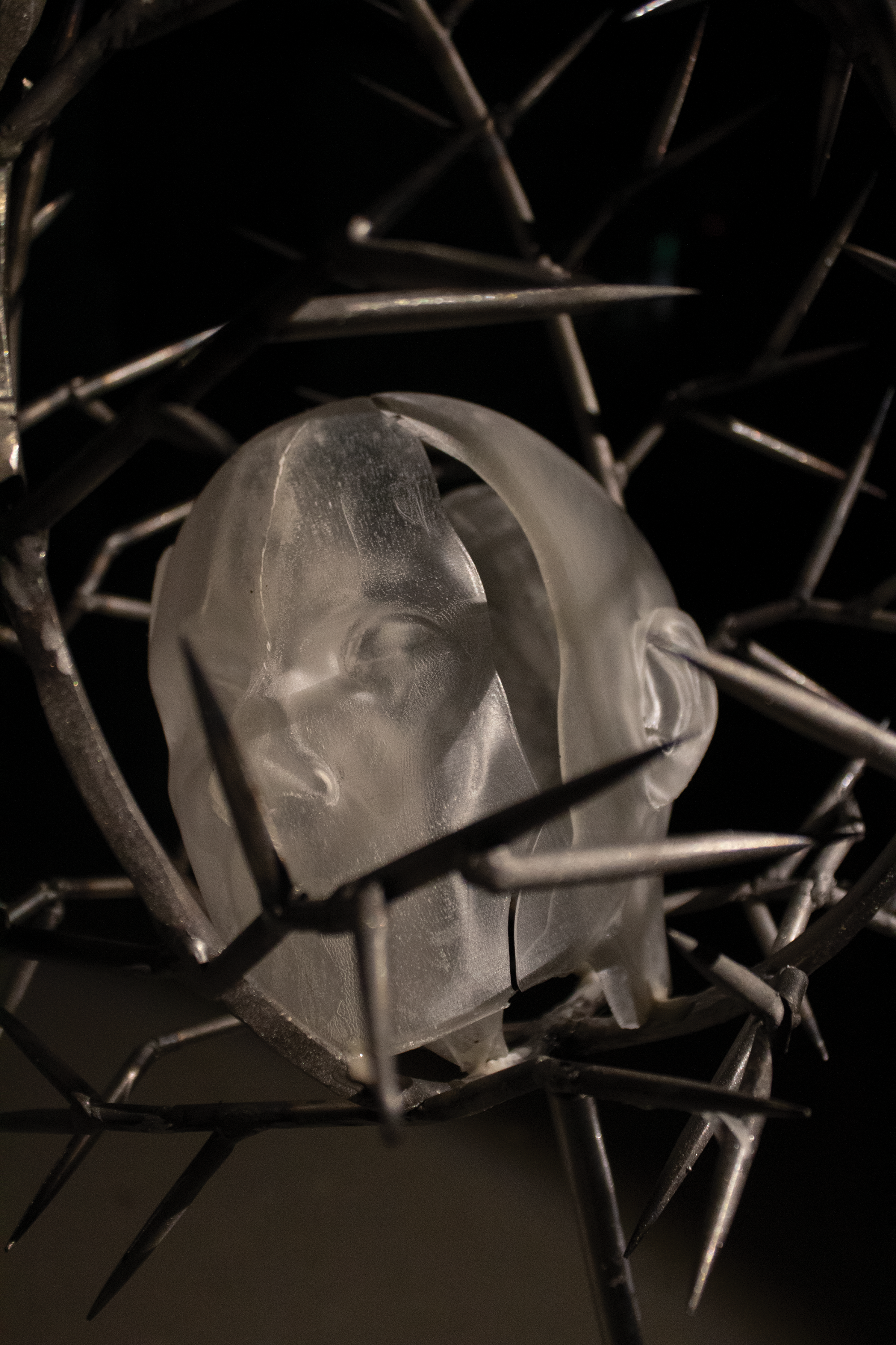 This work includes two standing pieces on the ground that are made of steel and liquid plastic. They are slightly tilted with spiky structures on the top. Inside of the structure, each has a casted human head that is made of plastic.