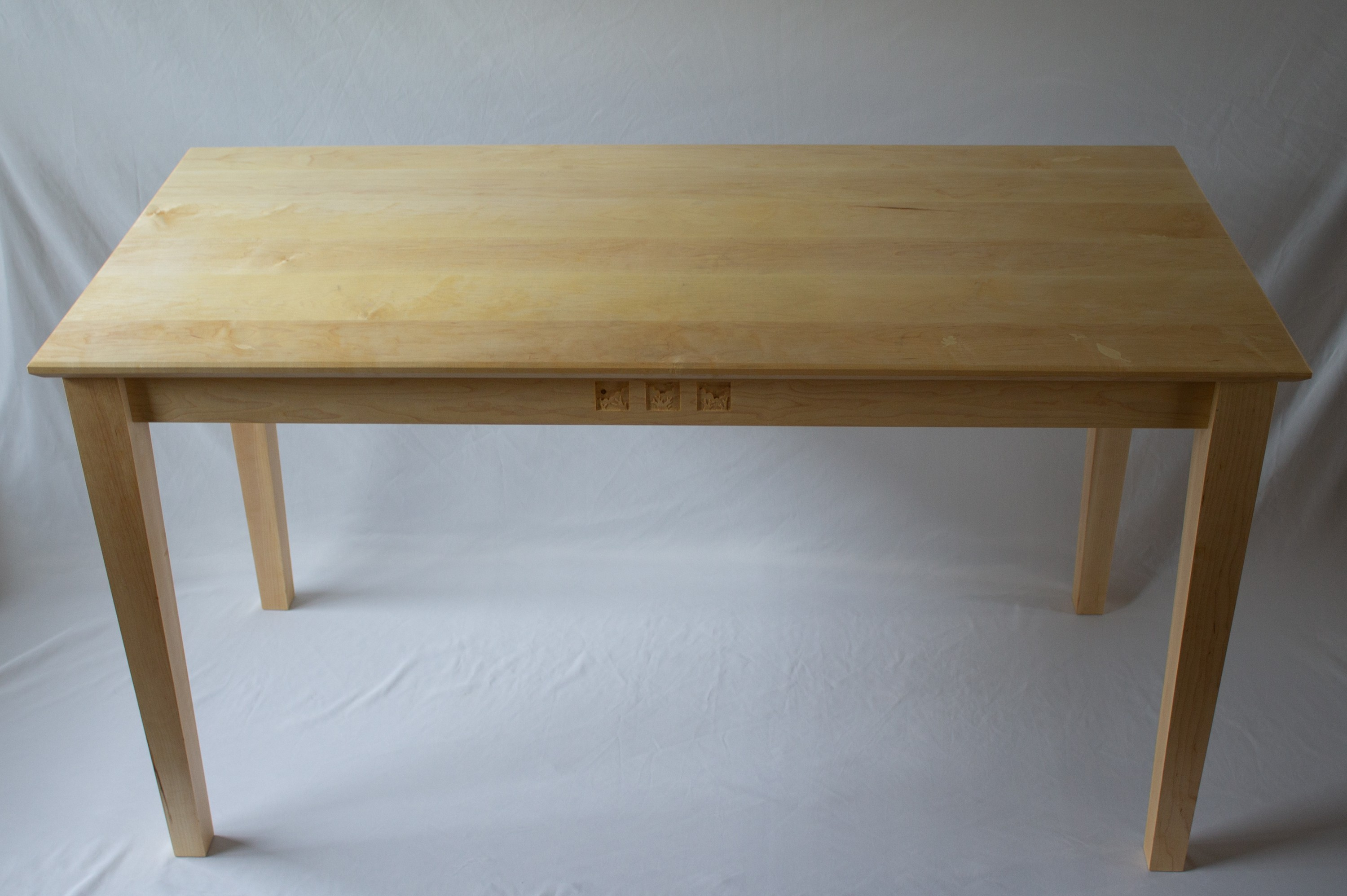 A writing desk made of hard maple. Blonde in color, the table stands on tapered legs and displays 3 scenic carvings on the front apron. The table-top has 13 maple wood leaf inlays and has chamfered edges.