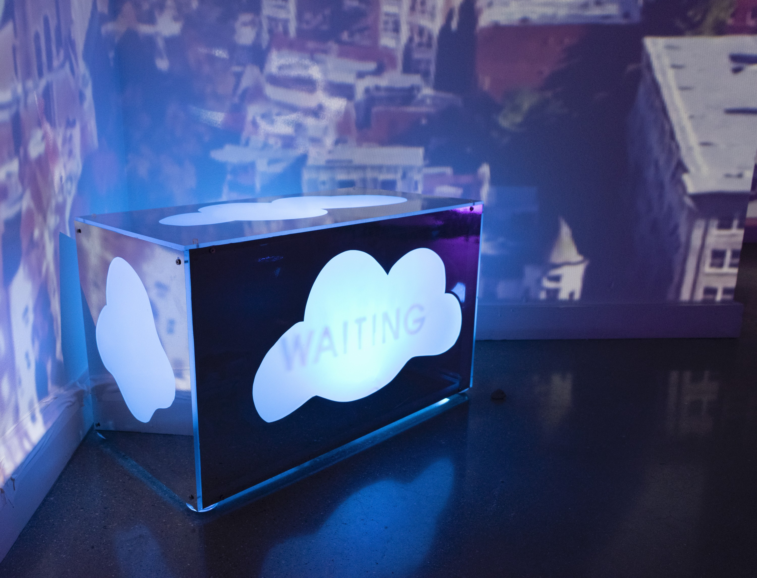 A rectangular cube positioned on the floor constructed of acrylic coated with a mirrored film. In ther center of each panel, a cut out in the shape of a cloud reveals a pulsating light beneath