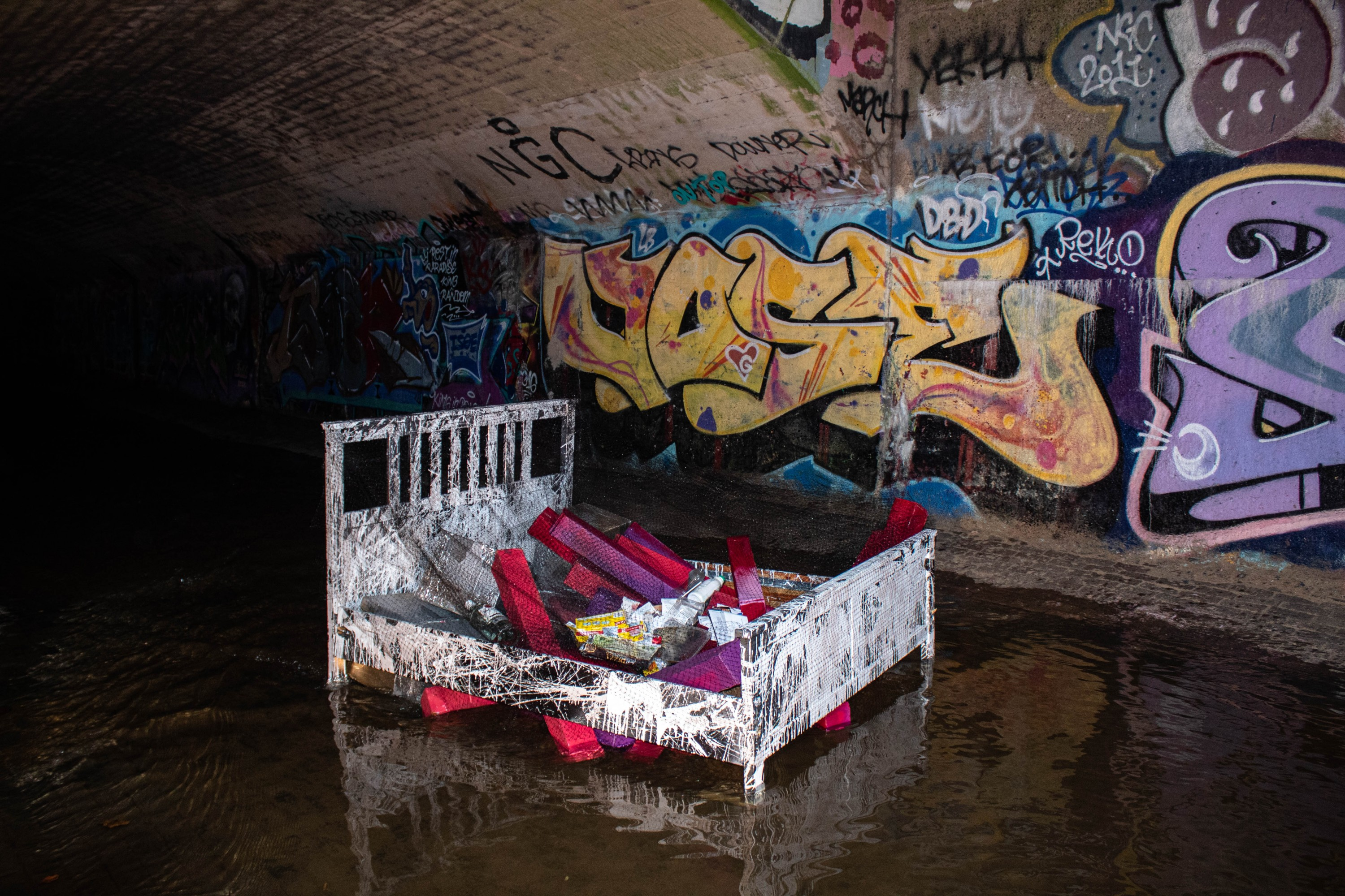 Painted bed frame and boxes topped with trash from the artist's consumption which is lackadaisically corralled with plastic netting reminiscent of a large fish net. Installation lived in Jones Falls stream tunnel laced in graffiti.