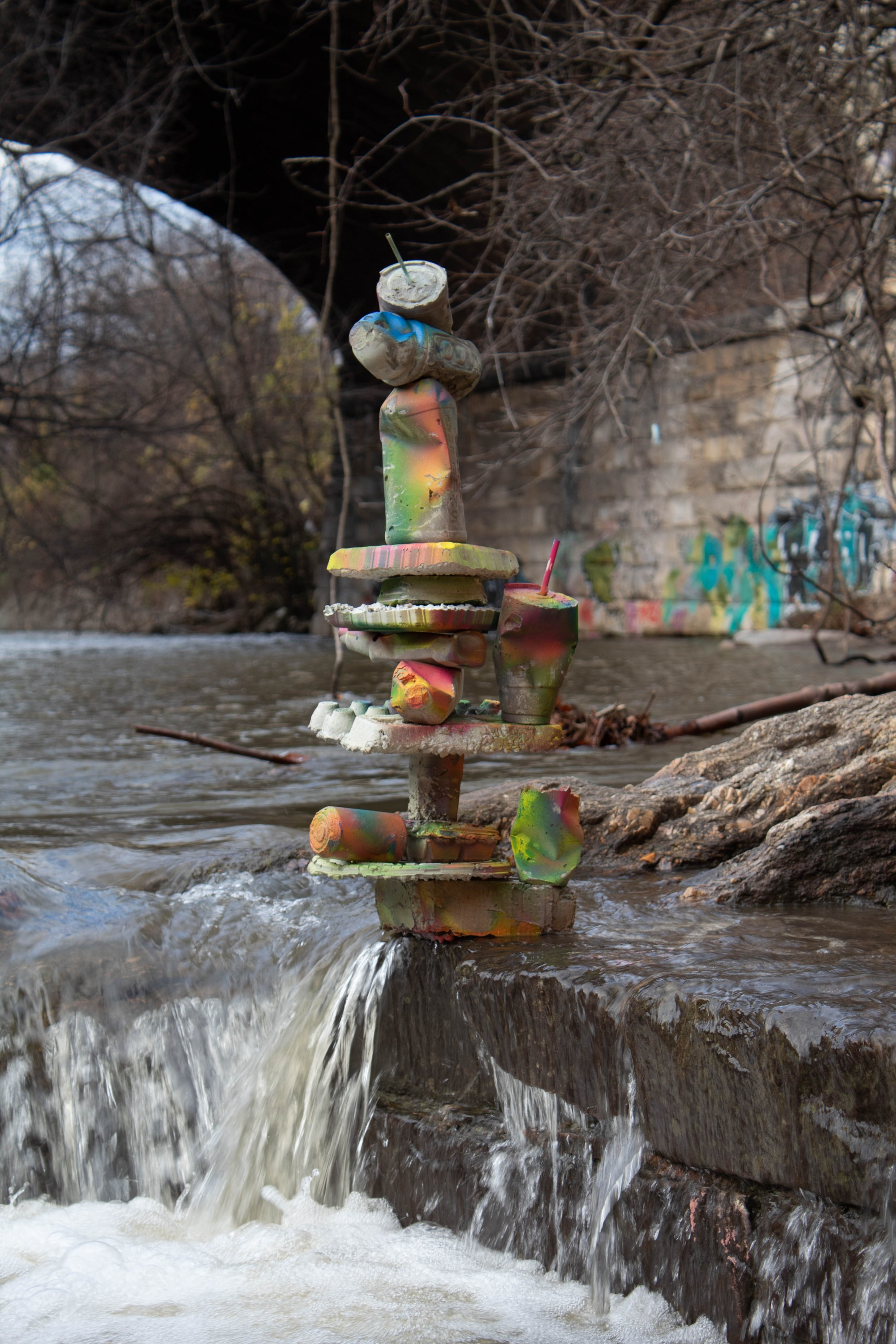 The first image of the three part series shows the consumer by-product concrete castings balanced as a graffitied rock cairn next to the Jones Falls stream.