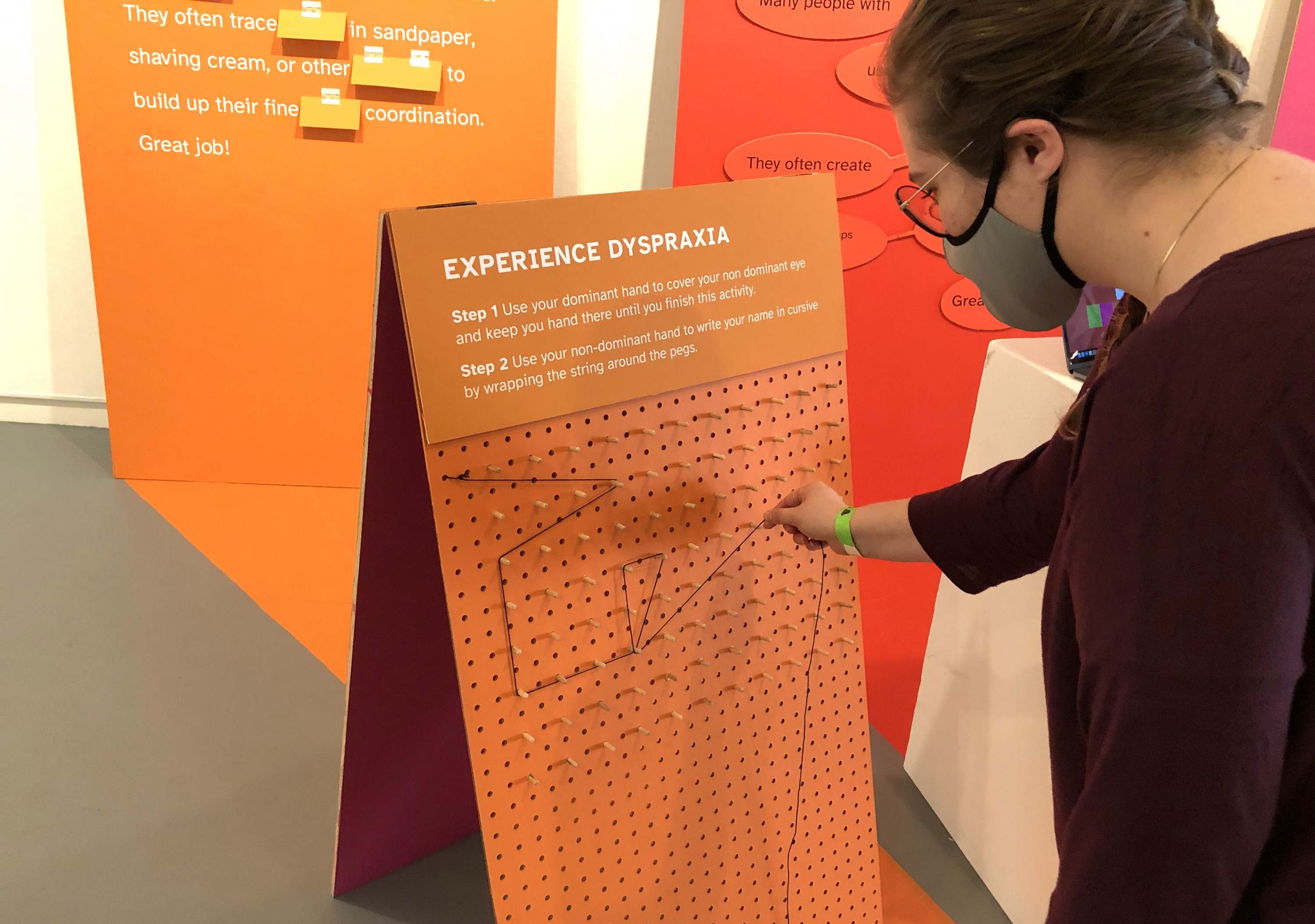 Visitors must struggle to write their name in string with their non dominant hand whyle covering one eye to simulate fine motor coordination issues that those with Dyspraxia often have.