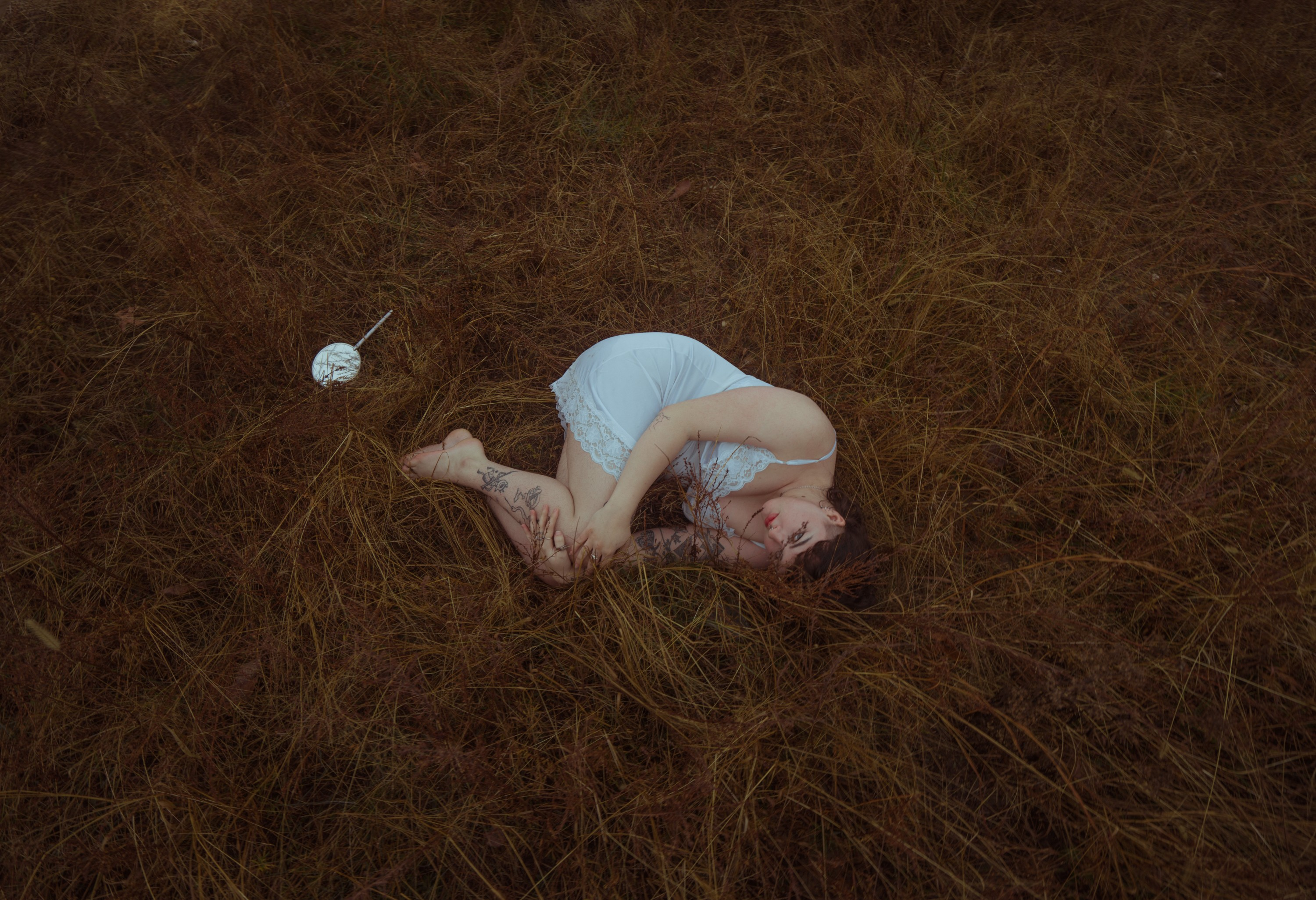 This is a landscape oriented digital photograph. The figure is in fetal position laying in tall, brown grass, wearing a white slip dress, looking at the viewer. A silver hand mirror sits on the grass to the left of her.