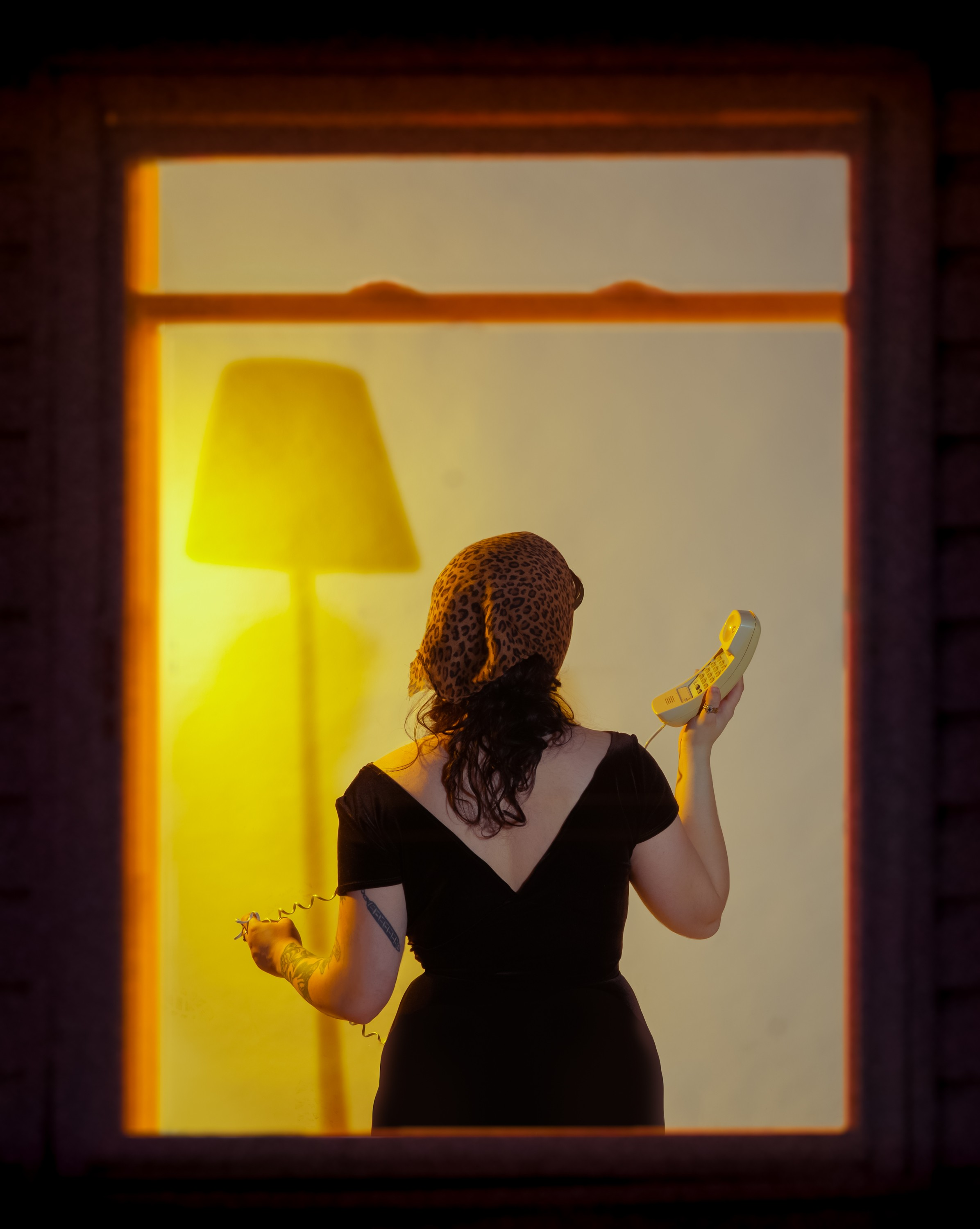 This is a portrait oriented digital photograph. The figure is seen from behind, semi-silhouetted against a warm interior – the viewer is looking through a window from the outside.