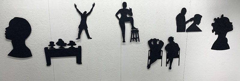 Handcut and Lasercut Handmade Black Cotton Rag Paper Installation of Black silhouette imagery.