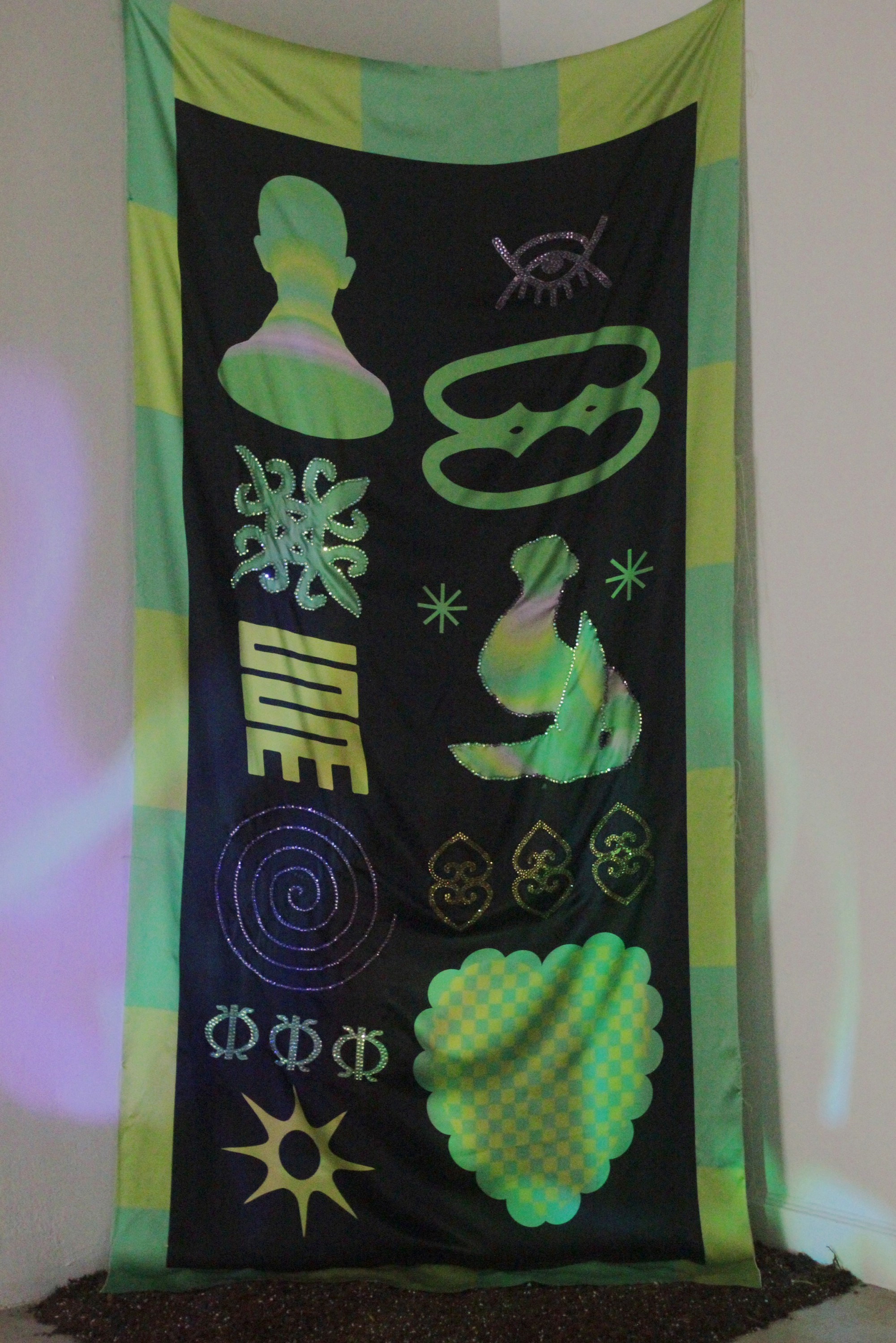 A 7.5 x 4 foot silk cloth with symbols digitally printed hangs in the corner of the gallery. underneath there is a circular pile of soil. The cloth is enclosed in a two-tone border in the style of Asafo flags in lime-green-yellow and seafoam-green-blue. T