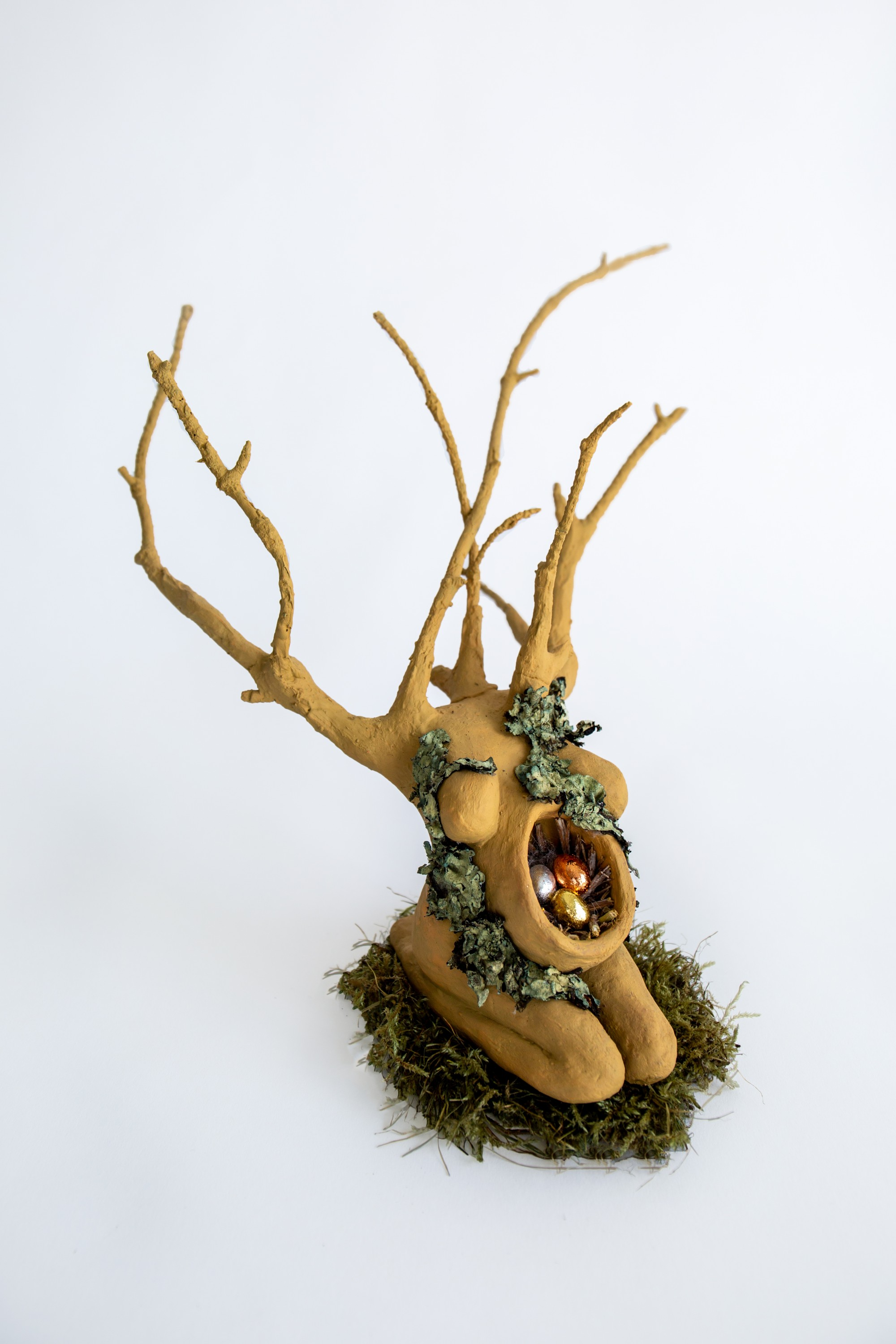 This figure is a pregnant Earth Goddess figure painted in a green hue, she kneels on a bed of green moss, lichen stretch over her body, her stomach is open with a nest inside and three eegs one copper, one gold, and one silver. Her body, from the arms up