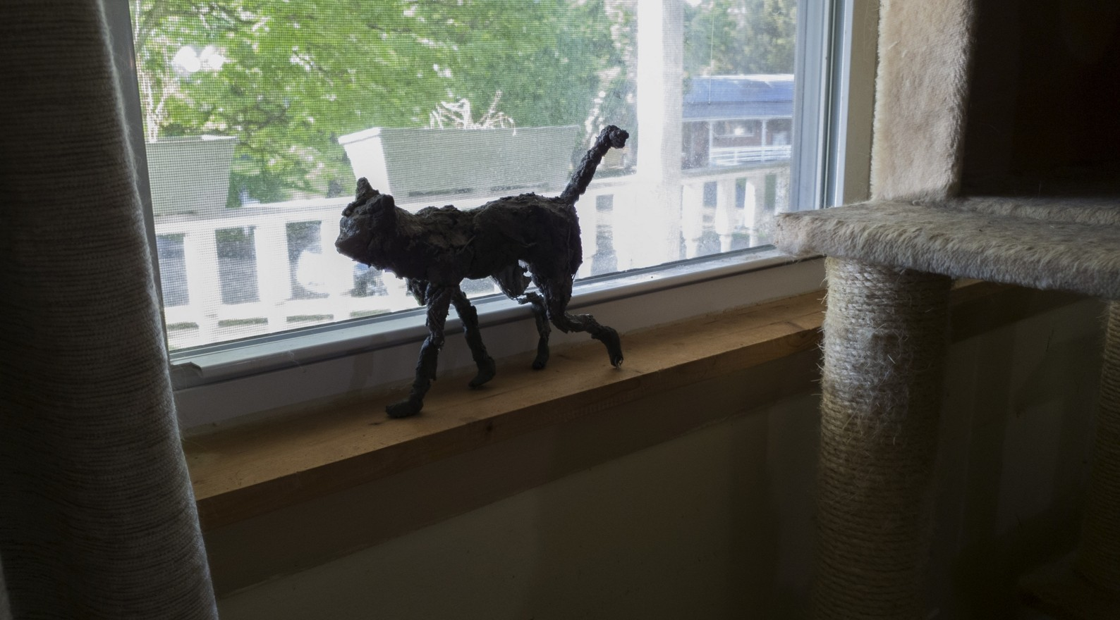 Photos of a roughly sculpted cat walking across a windowsill and the floor.