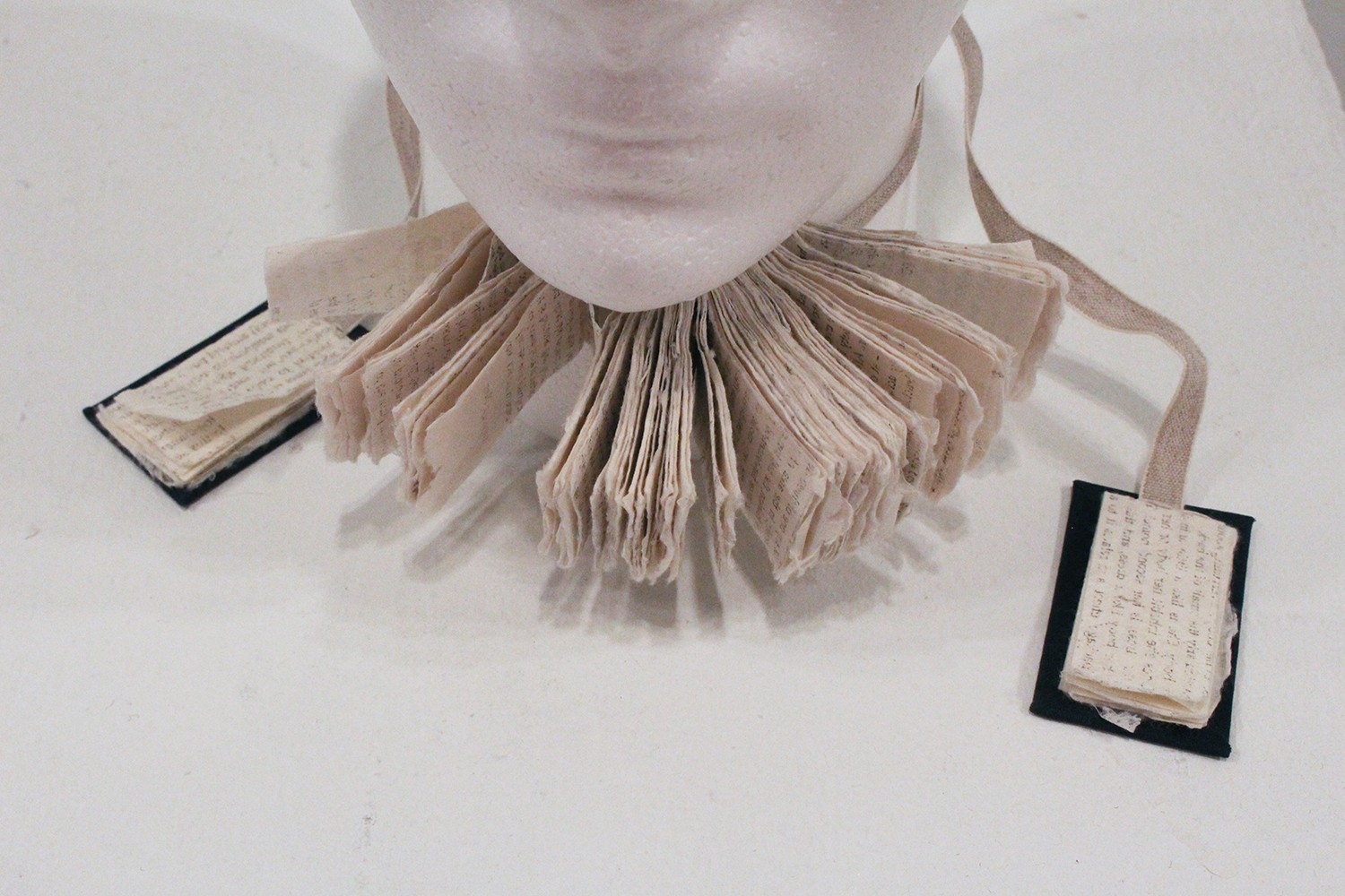 """This series begins with """"The Choker Book,"""" which explores how books and knowledge come against us. When wearing this book as a choker, the pages turn outward. In this way, instead of serving as an object with reading functions, it becomes unreadable bonda"""