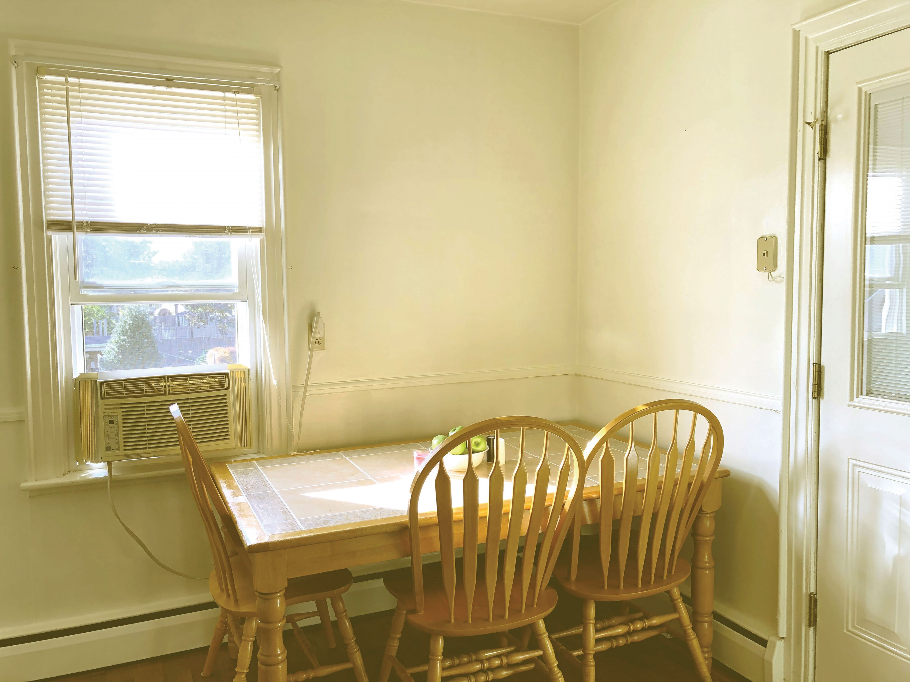 A photo of a kitchen table and chairs, situated in the corner of the kitchen with a bowl of green apples on top. There is a window to the left of the table, with sunlight streaming into the entire room.