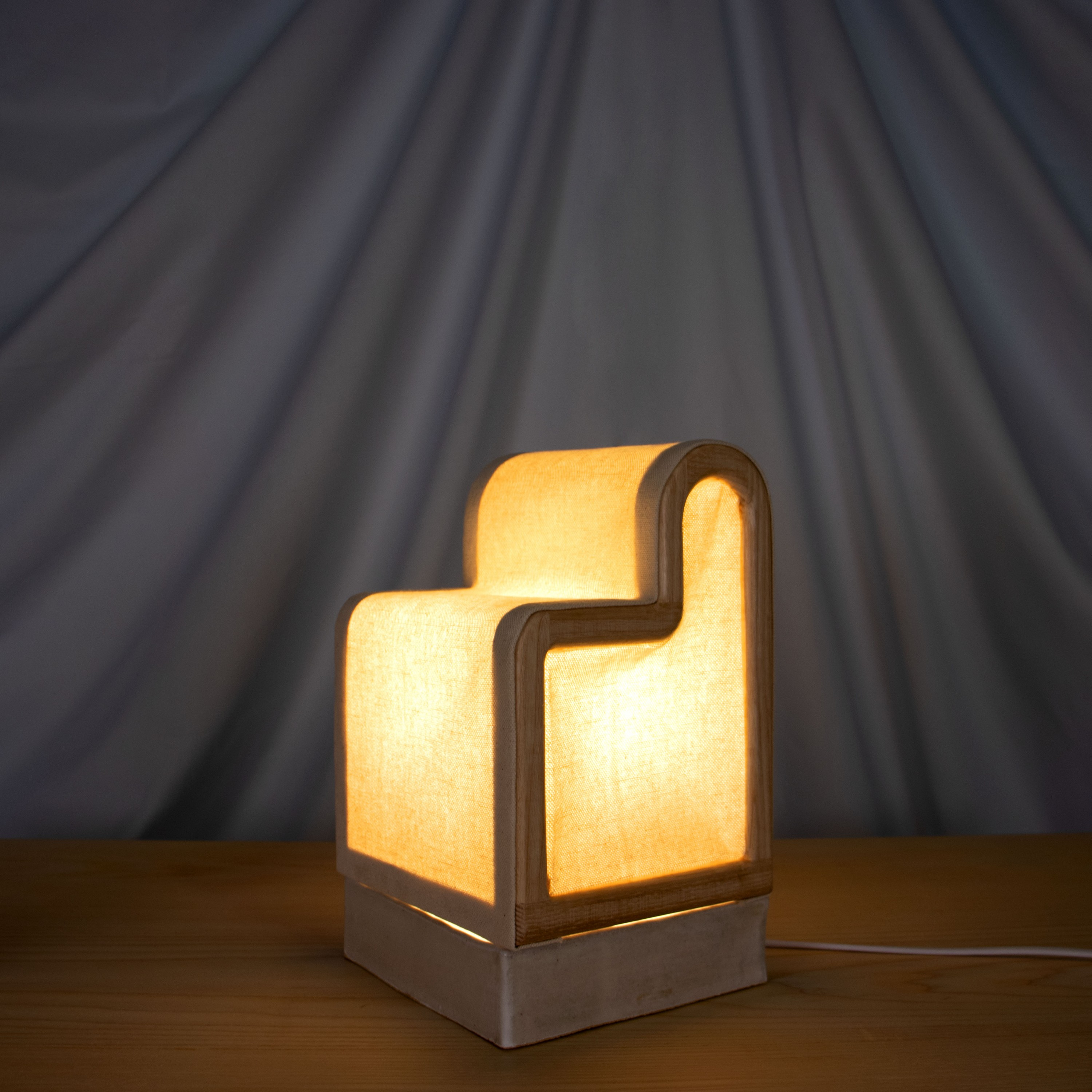 A lamp with a square, ceramic base and a shade consisting of an ash wood frame and wrapped canvas is placed on a wooden tabletop in front of a blue fabric background. The lamp is illuminated, making the image very moody and dramatic. The shade is a rounde